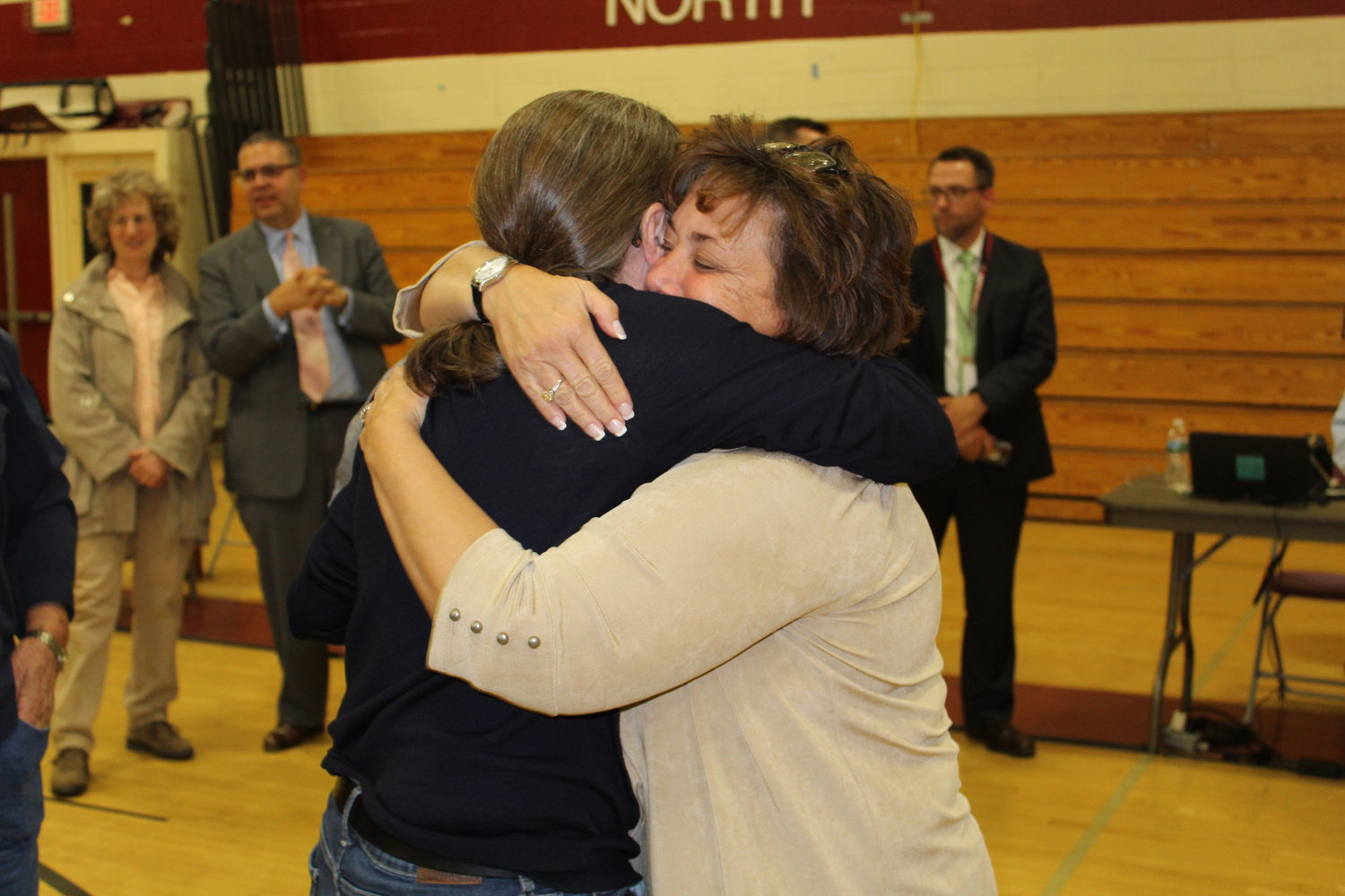 Former school board trustee Amy Beyer, right, hugged her friend Sara Jones, who was re-elected to serve on the North Shore Board of Education Tuesday night. Jones, of Sea Cliff, is the president of the school board