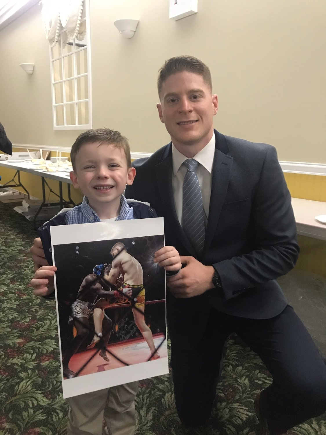 Campbell, right, is a former Lynbrook Titans wrestler, and spent time with current Titans wrester Jack McAssey, 6, at the program's annual awards ceremony in March.