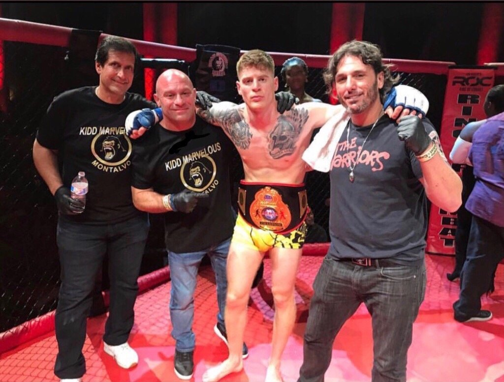Campbell, wearing the International Sport Karate Association New York MMA championship belt with, from left, coaches Ray Longo, Matt Serra and Eric Hyer, who have helped prepare him for the fight.