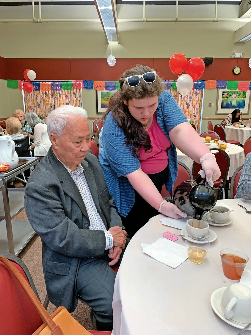 Glen Cove High School freshman Michaela Adam, 15, served Kam Yuen, 95, some coffee after dinner.