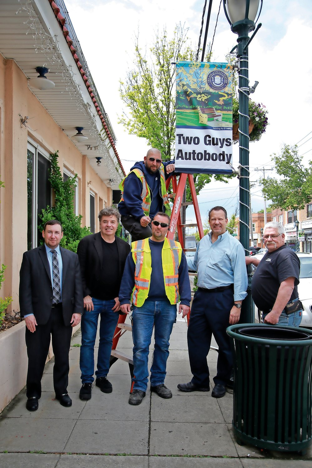 Chamber President Dominick Minerva, from left, artist Michael Stanko, Tony Ragusano, Gerald Scarangella, Mayor Ed Fare and Brian Howley hung the banners on Rockaway Avenue on May 23.