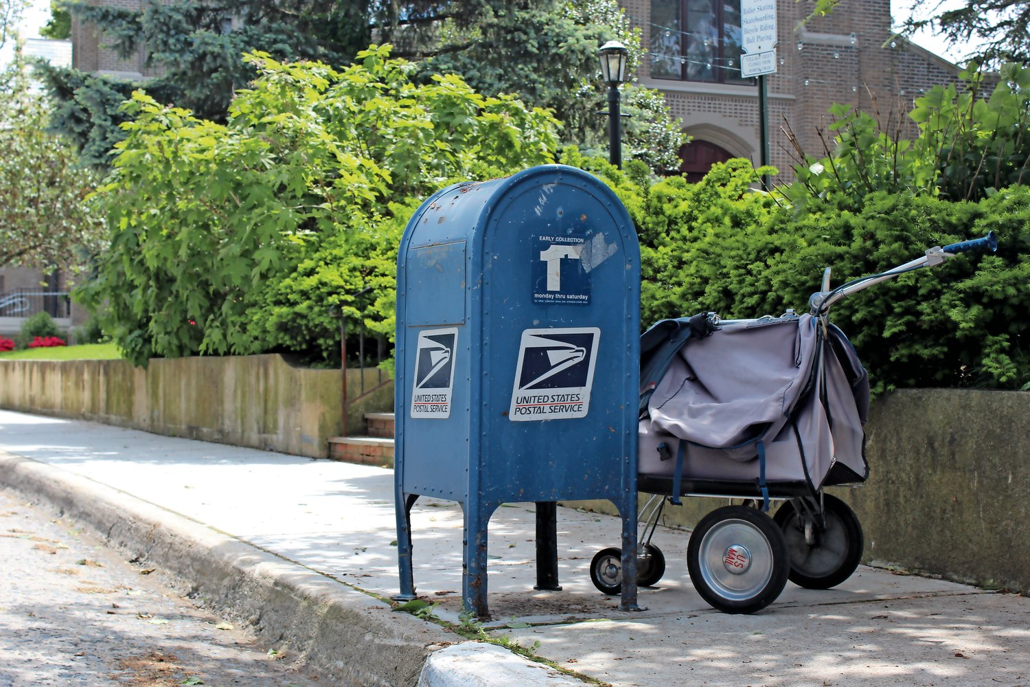 A mail carrier bag sitting unattended next to a traditional mailbox near Sea Cliff's Village Green.