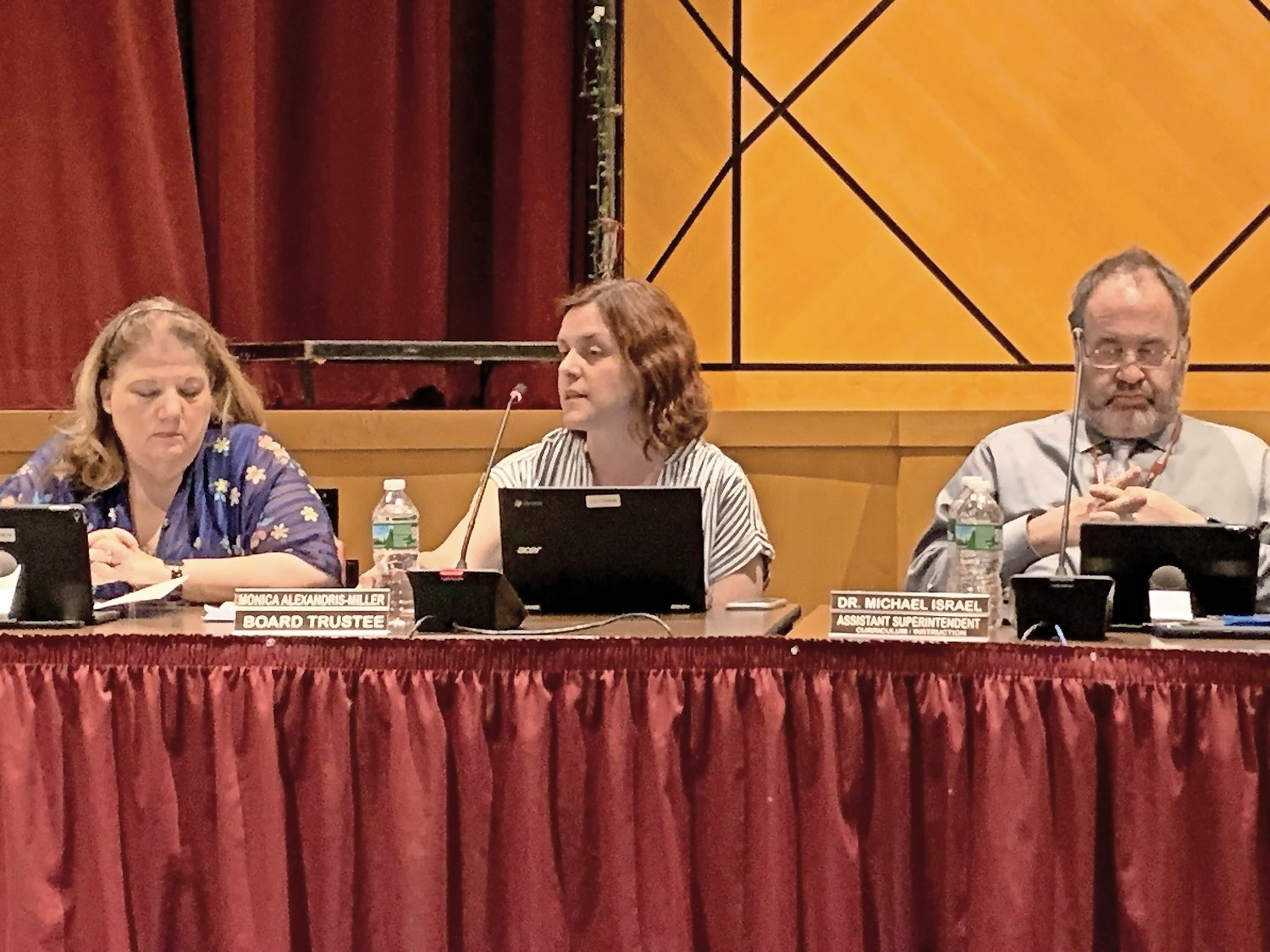 Trustee Mary Murphy and Dr. Michael Israel, an assistant superintendent, listened as Trustee Monica Alexandris-Miller, center, stressed that the bond needs to be crafted now.