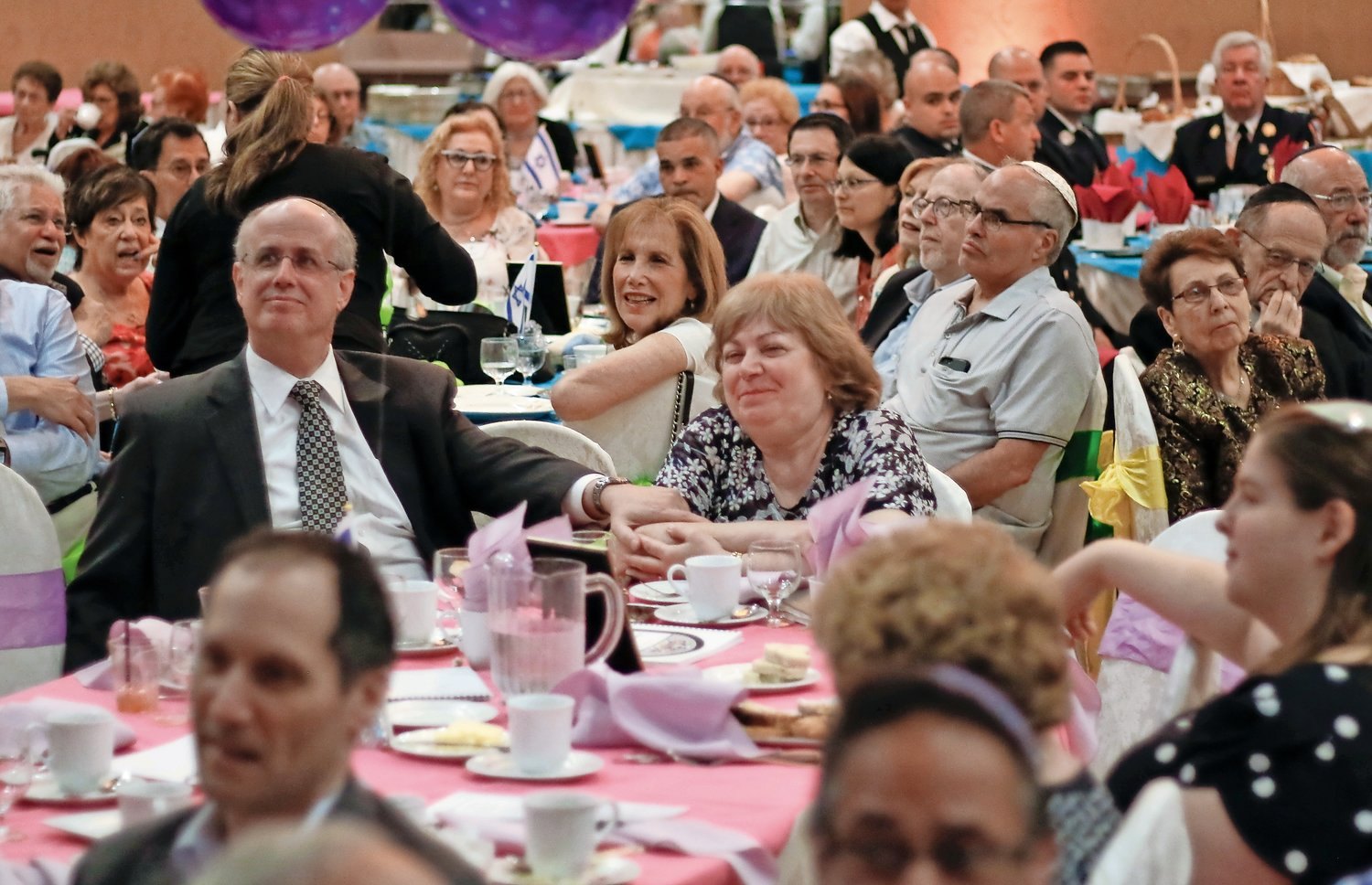 Loved ones, friends and congregants surrounded Rabbi Mark Greenspan, left, and his wife, Marilyn, as they celebrated his 22 years in the community on Sunday.