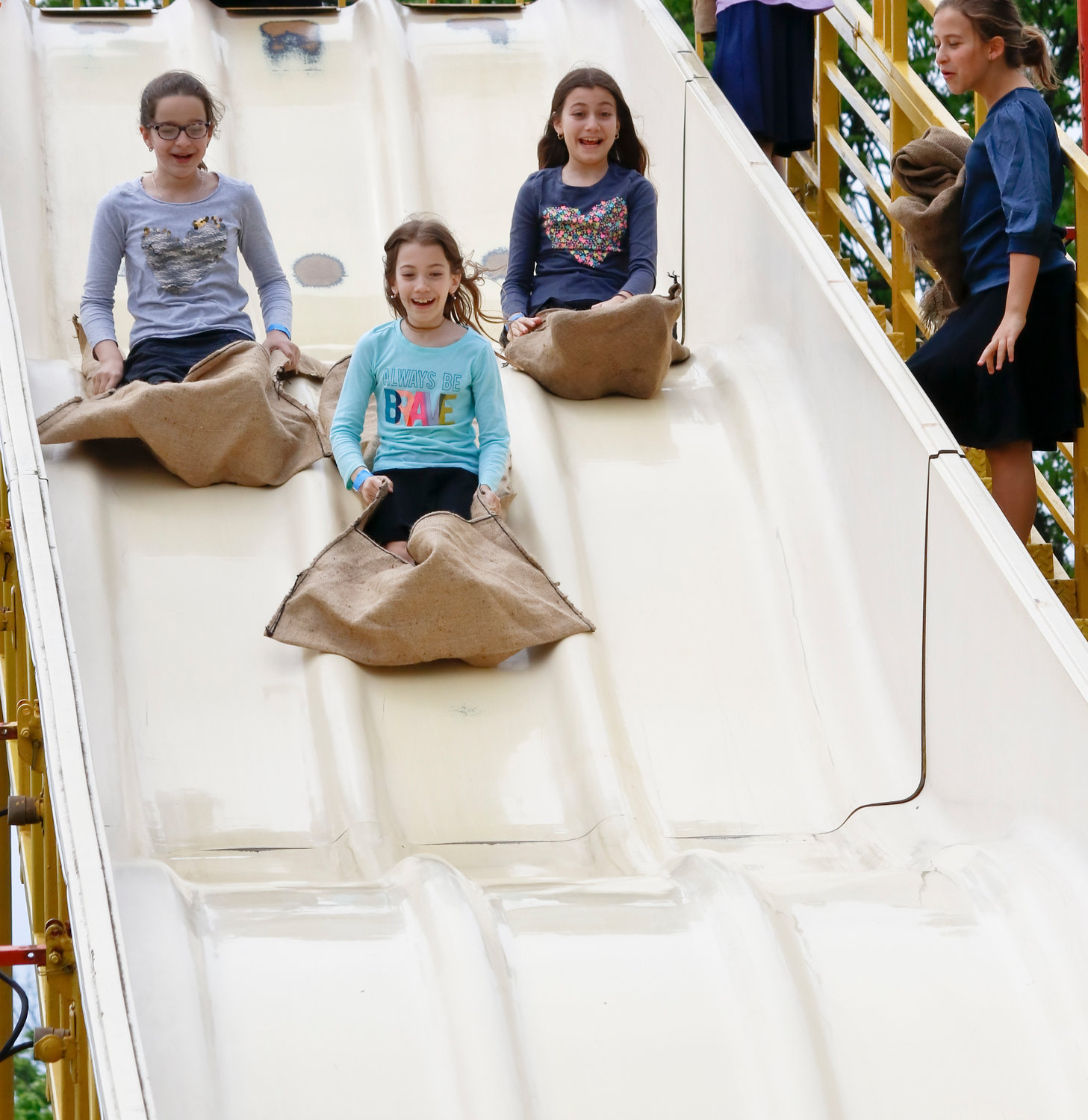 The slide was one of the more popular rides at the Kulanu Fair in Andrew J. Parise Cedarhurst Park on May 19. Shulamith School students from left, Rena Gelbstein, Meira Moskowitz and Ahuba Moskowitz all appeared to enjoy downward trip.
