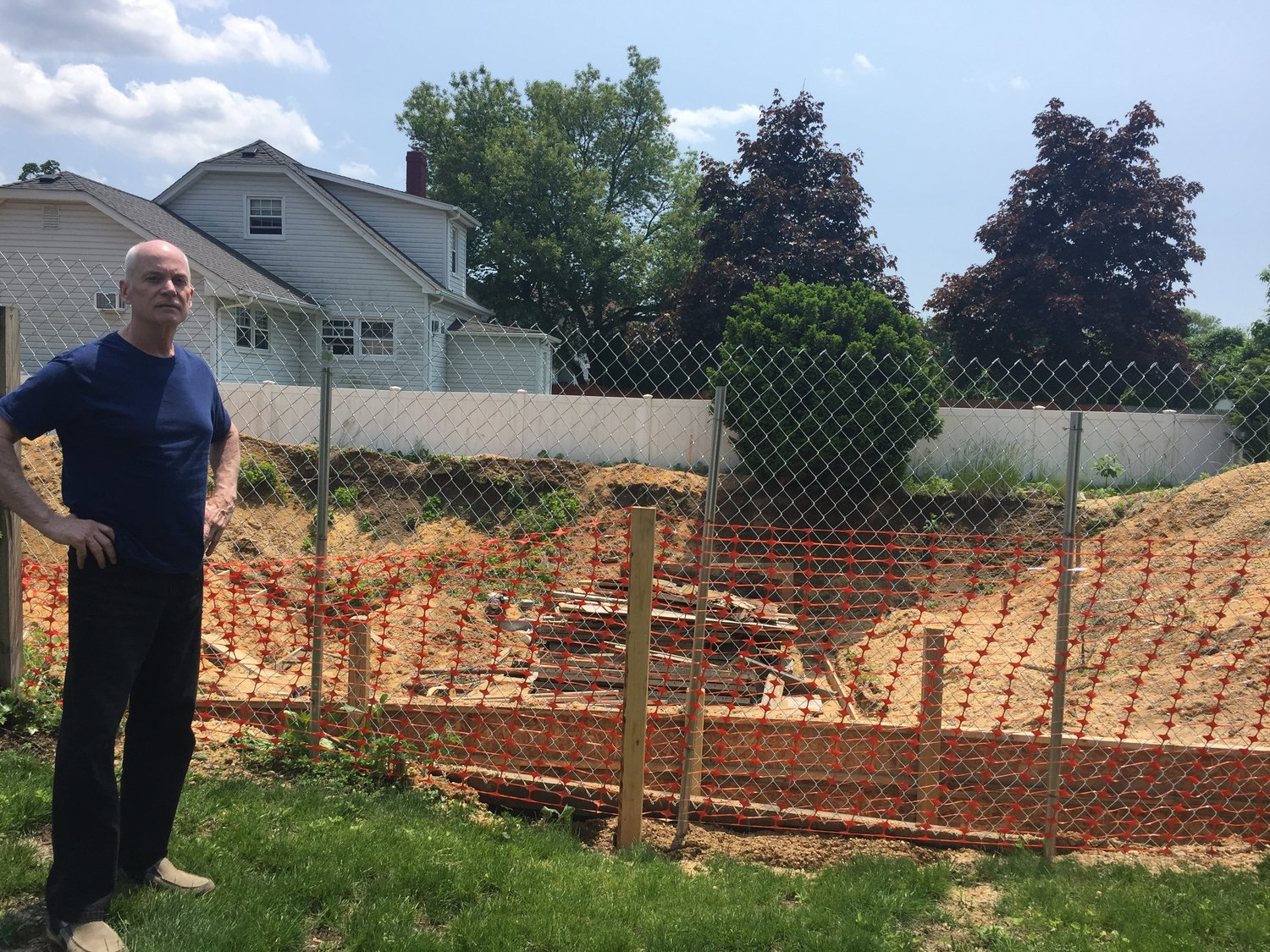 North Bellmore resident Daniel Butler stands next to the hole that has caused part of his backyard to collapse.