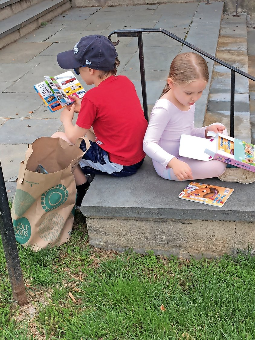 "Jack and Vivienne Cave shared some quiet time on Garage Sale Day after picking up books from the Friends of the Sea Cliff Library's ""Giant Gently Used Book Sale."""