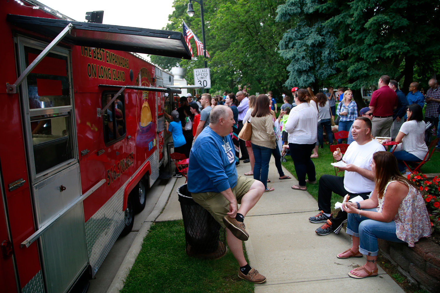 Crowds of people waited on lines for Empanada Queen and Neapolitan Express Pizza food trucks.
