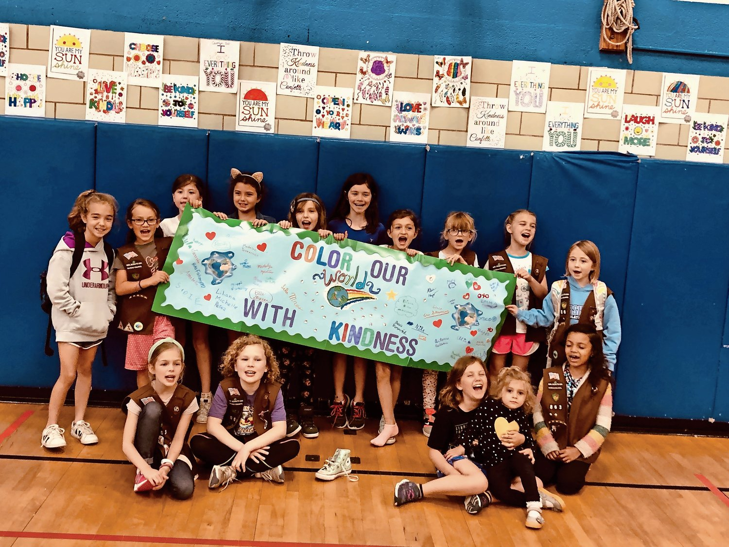 "Students from Brownie Girl Scout Troop No. 863 held the ""Color Our World With Kindness"" banner."