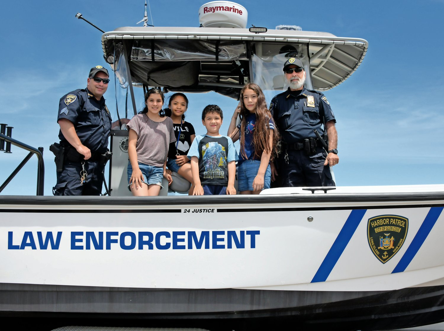 Barbara Benitez, second from left, Halley and Axel Aquilaz and Isis Jackson joined Harbor Patrol Sgts. Michael Anthanasio, far left, and Russell Lerch on the patrol's newest boat.