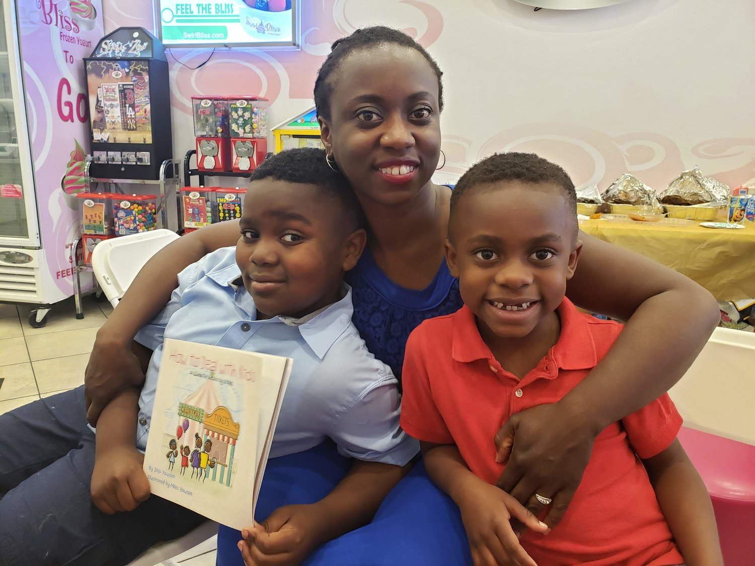 "Jojo Yawson, 9, left, showed off his debut book, ""How to Deal with Kids."" His 6-year-old brother, Miles, right, worked on it with him, and their mother, Ama, helped them publish it."