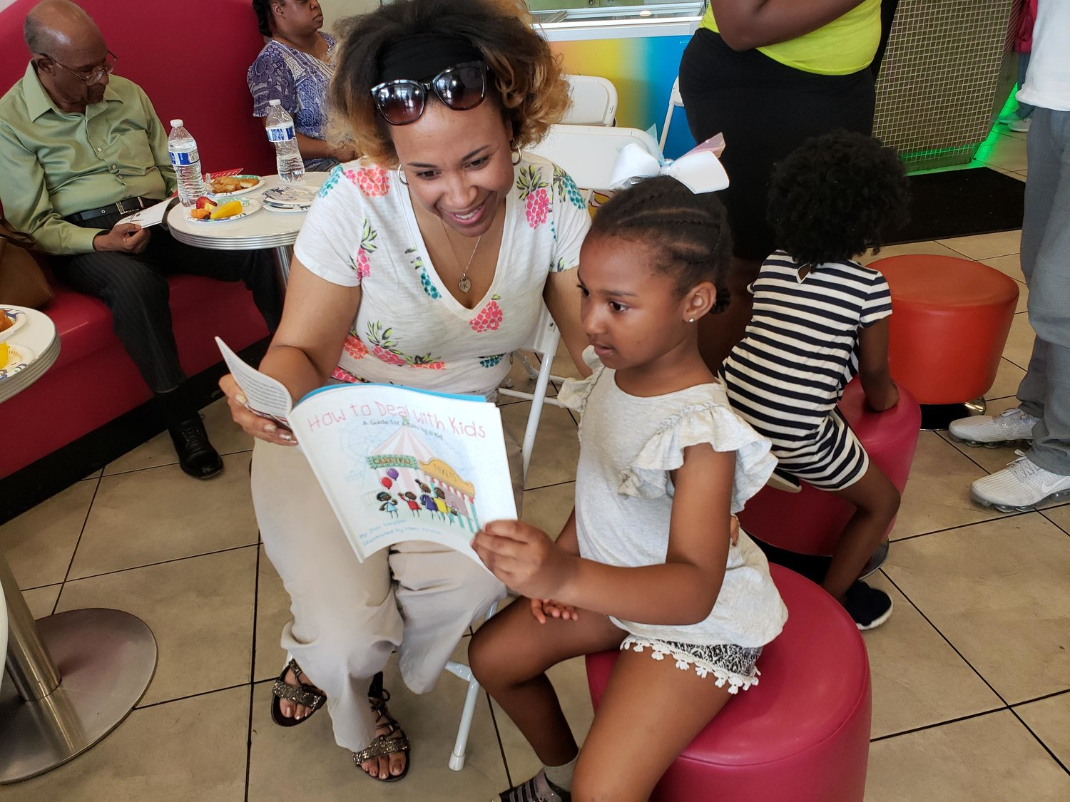 Baldwin Harbor mom, Katrina Graham, left, listened to her daughter Aleeyah, 6, read pages of the book after Jojo Yawson's presentation.