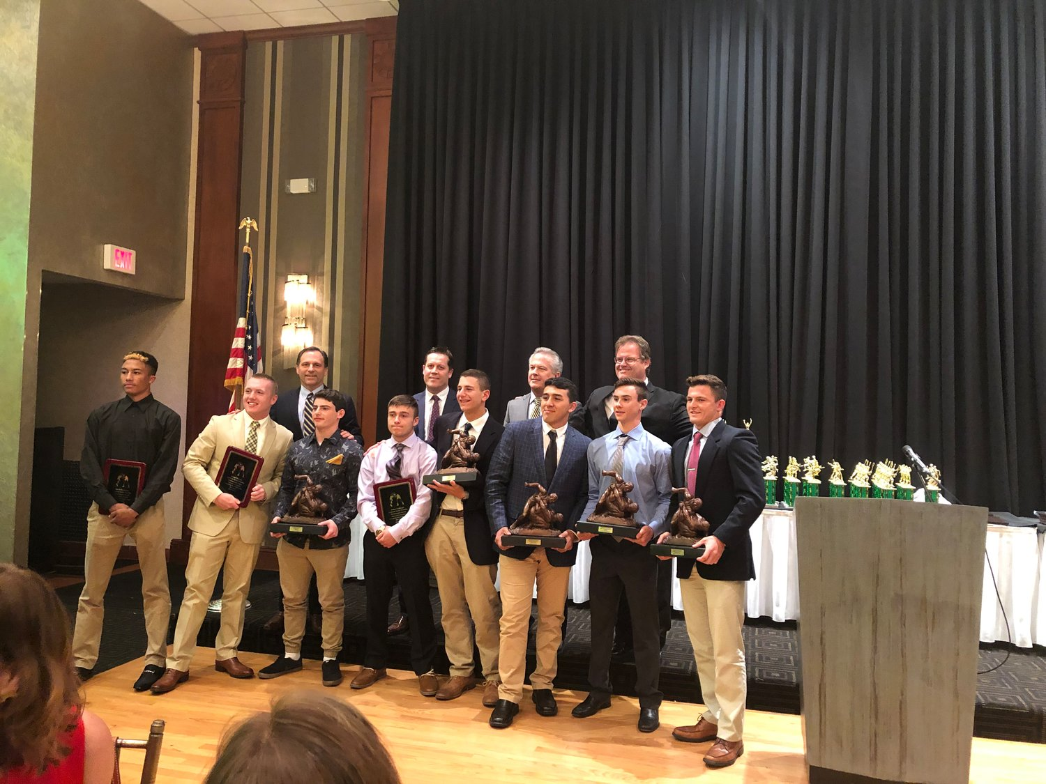 Lynbrook High School varsity wrestlers who were recognized at the annual Becker Brothers Awards ceremony included, from left, David Frederick; Jimmy Murray; Tyler Heaney; James Guillespie; Jessie Candel; Henry Quilca; Justin Weinberger; and John DiBenedetto. Above, the wrestlers with, from left, Hilary Becker, coach Matt Hollenstein, Greg Becker and coach Rich Renz.