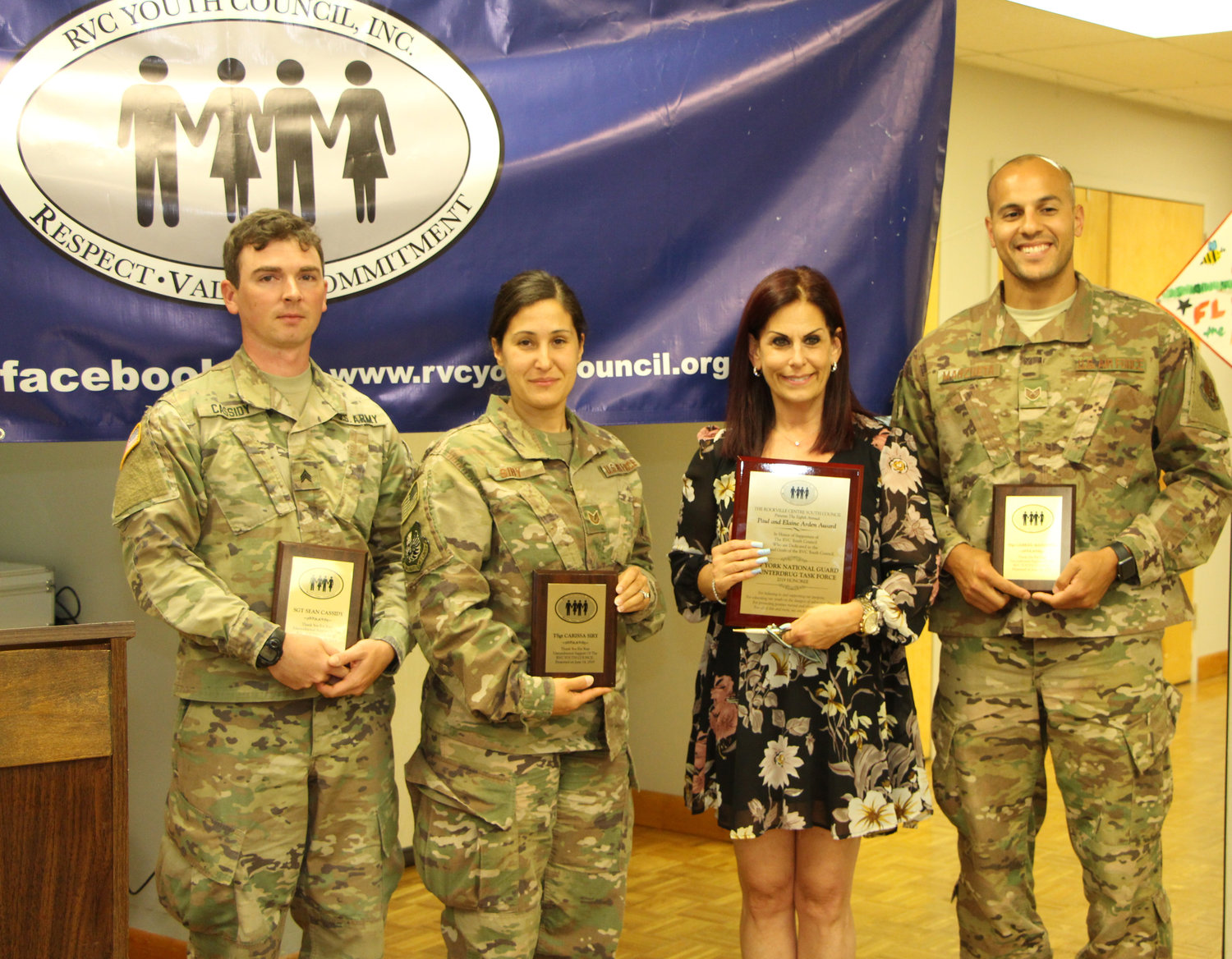 Sgt. Sean Cassidy, from left, TSgt. Carissa Siry and SSgt. Gabriel Marizueta, members of the New York National Guard Counterdrug Task Force, joined Andrea Connolly, who presented them with awards.