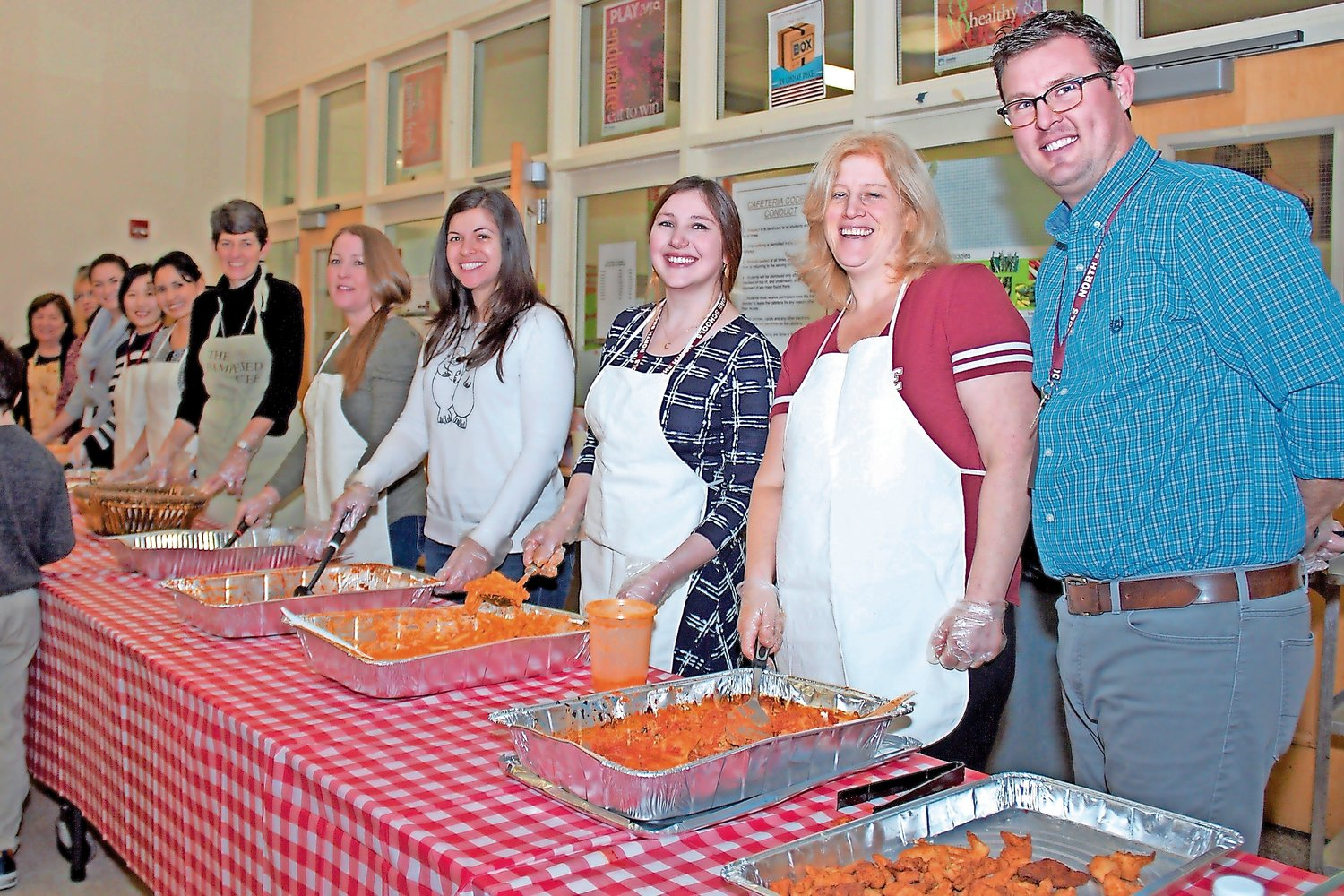 Nimmo far left, joined other faculty members to serve food to families at the school's annual pasta and game night event.