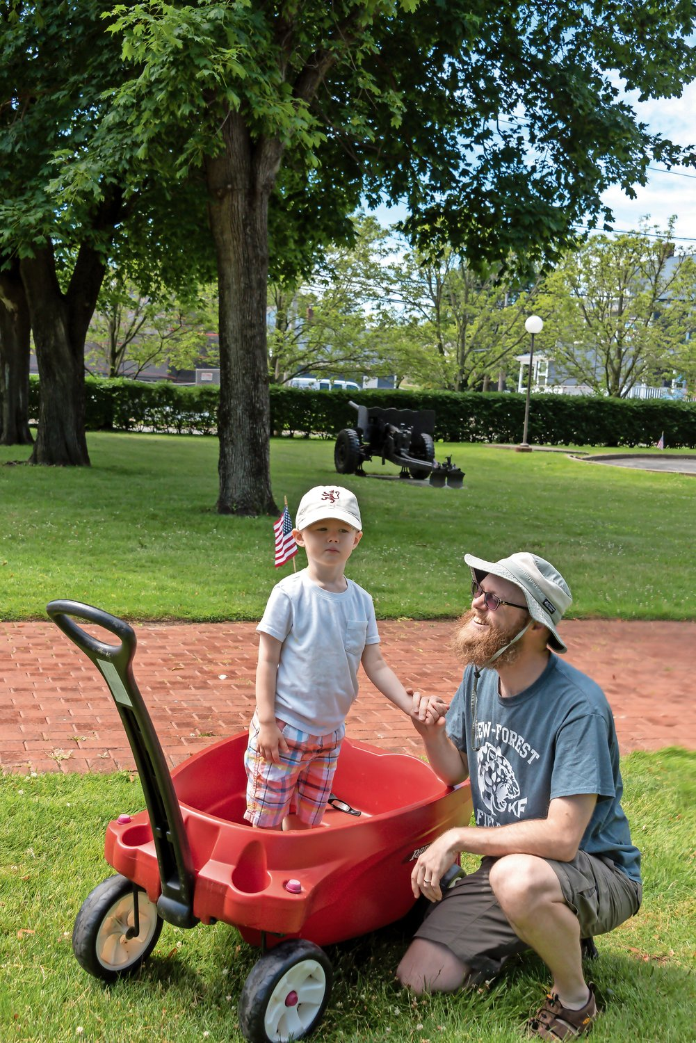 Colin Sipley, 3 ½, stood on the seat of his wagon to get a better look at the action with his father, Tristan Sipley.