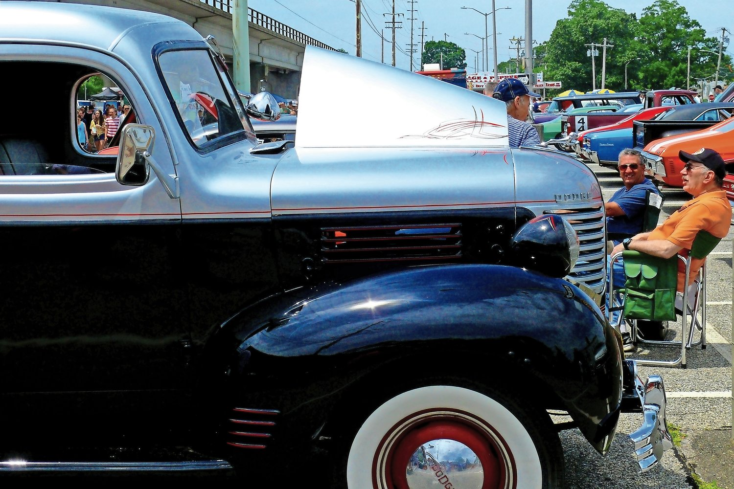 At the car show's close, classic car owners traded stories while their steers baked in the sunlight with their bright and colorful paint jobs.
