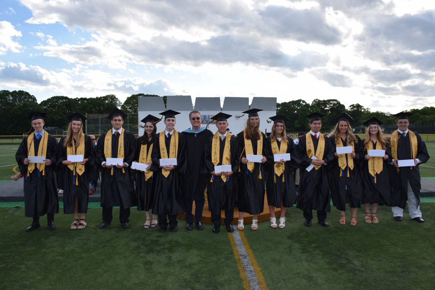 Wantagh Dollars for Scholars Scholarship Fund President Gerald McCrink, center, presented 12 graduates with scholarships.