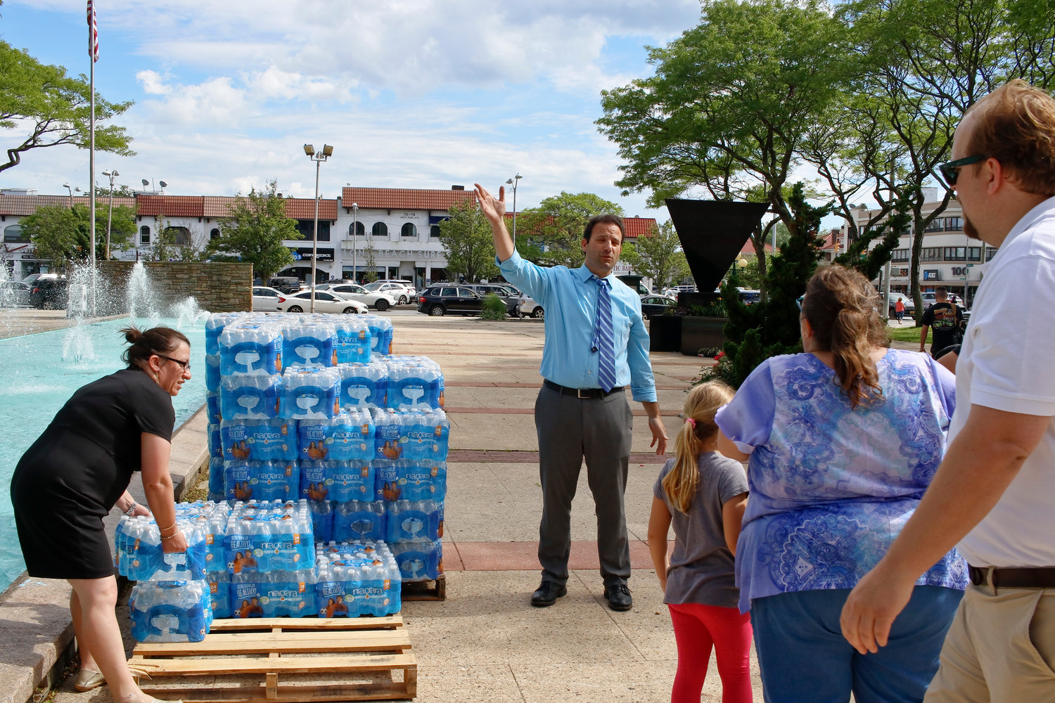 City Council Vice President Chumi Diamond, left, and Council President Anthony Eramo, center, distributed bottled water at Kennedy Plaza on Friday.