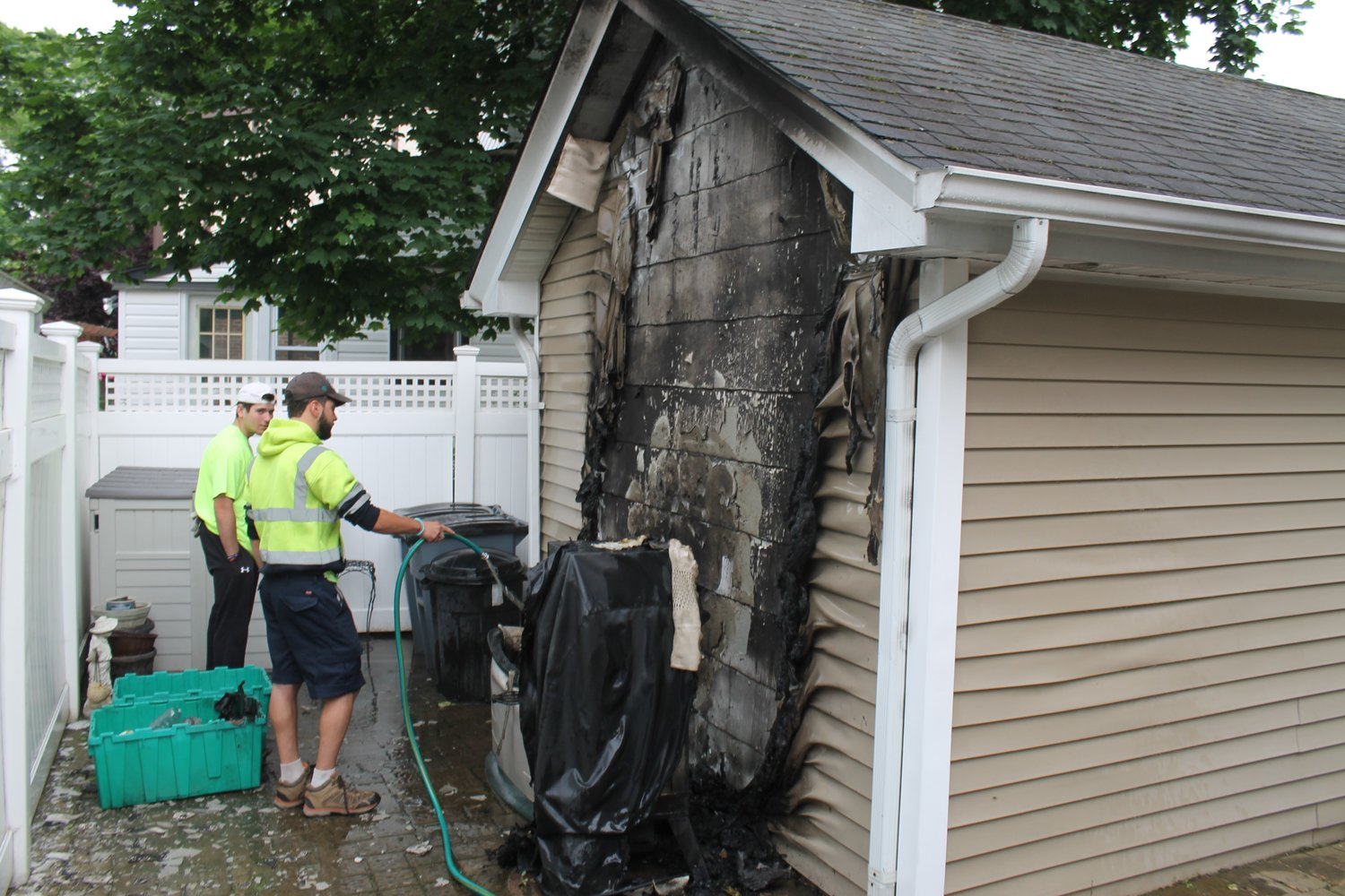 Lynbrook Department of Public Works employees Aidan Ryder, left, and Charlie Curcio helped extinguish a fire that was consuming the back of the garage of a house on Sherman Street and Blossom Heath Avenue.