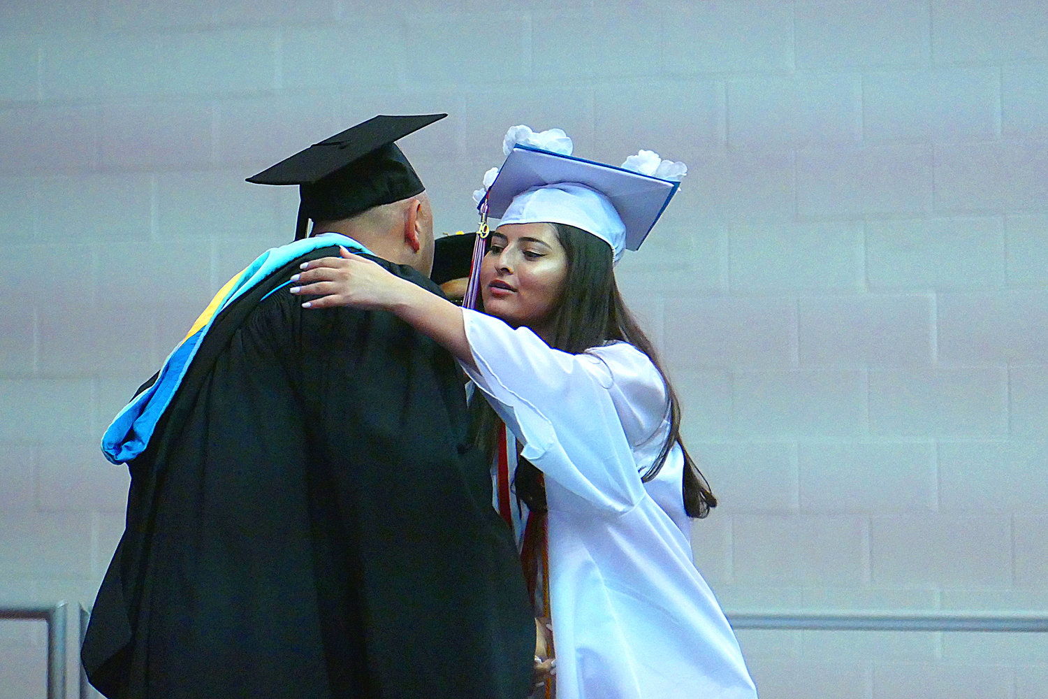 Valedictorian Leah Hochman, far left, hugged Principal Joseph Mille after receiving her diploma.