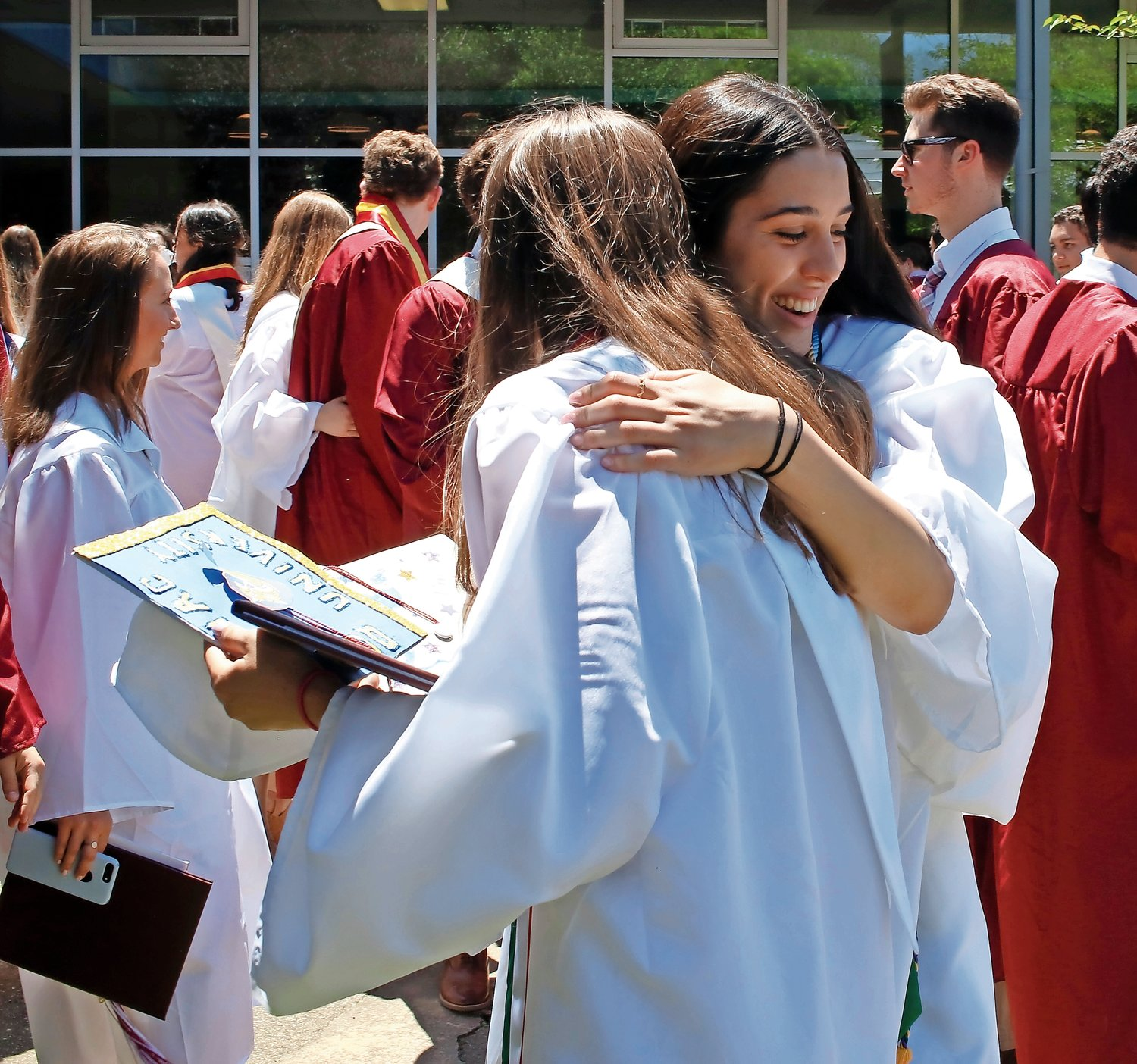 Cristina D'Amico, right, ran threw the crowd to hug her friend Alexandra Caldwell. They both graduated with seals of biliteracy and high honors.