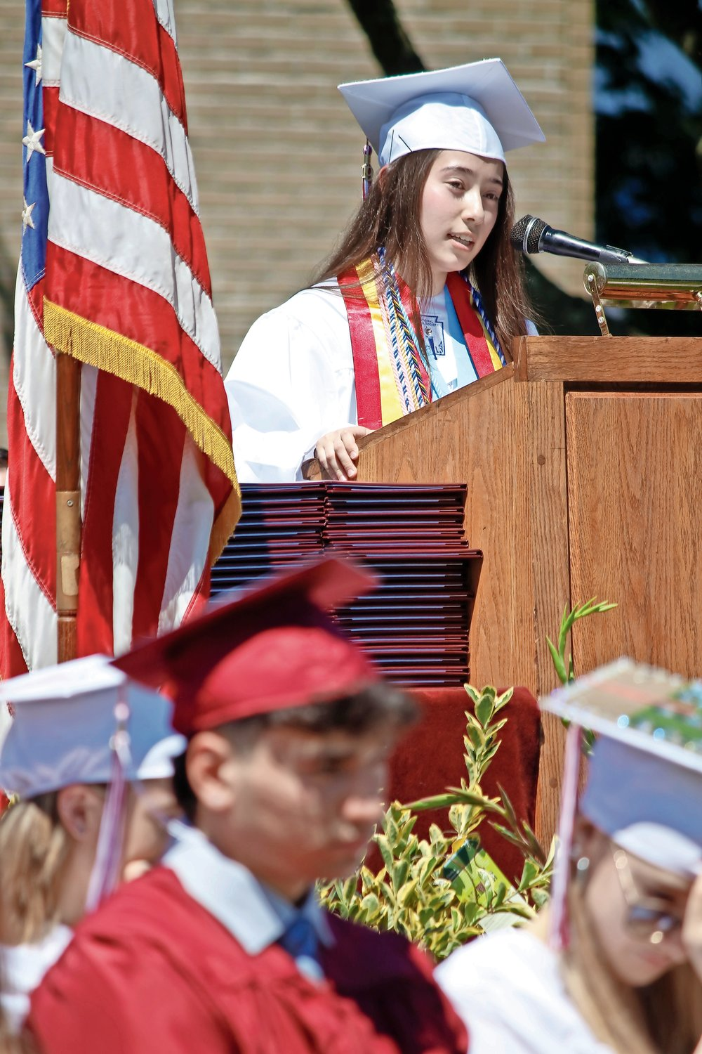 Salutatorian Hanah Leventhal, adorned in multiple honor cords, addressed her fellow graduates.