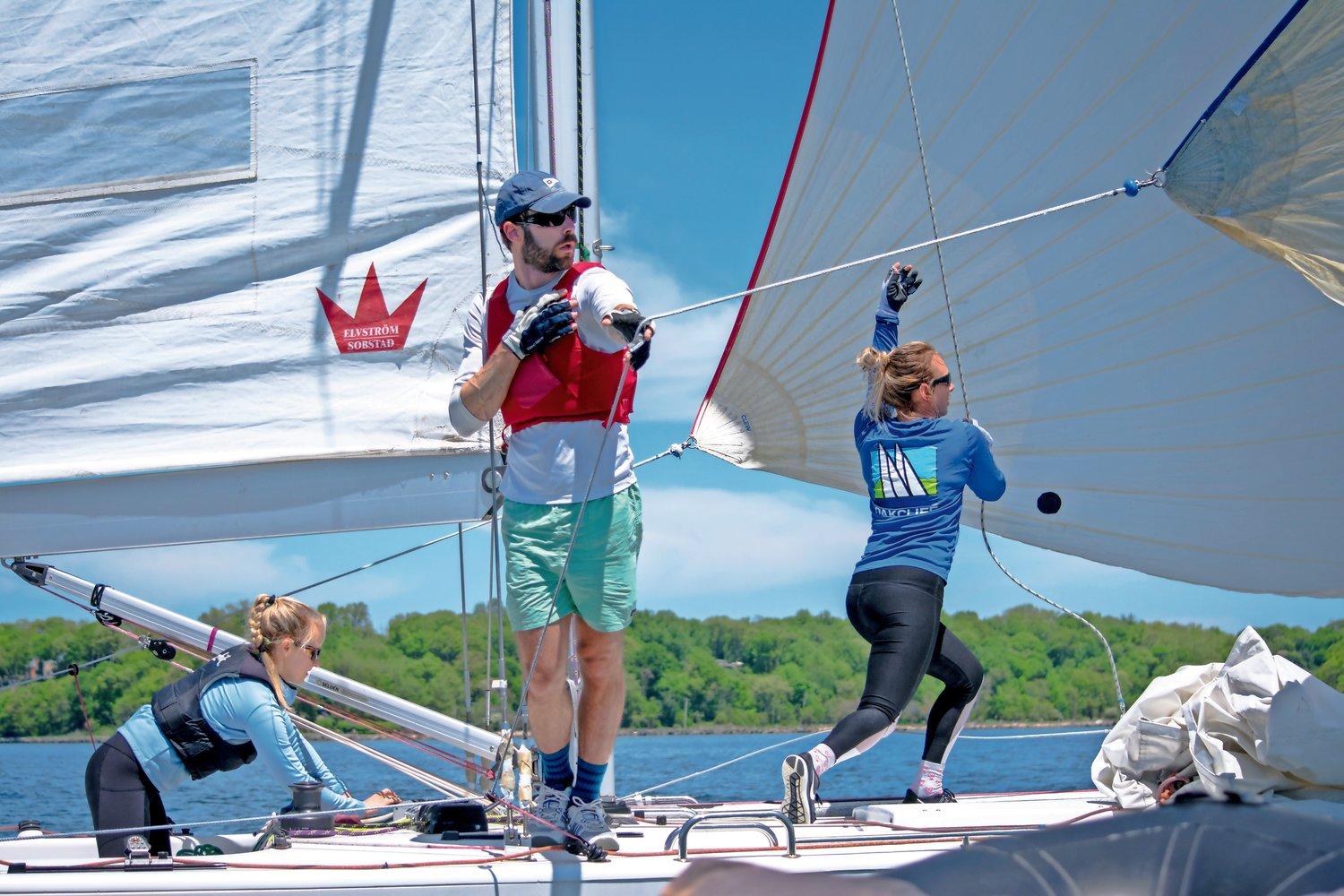 Myles Cornwell acting as a human pole during the team's spinnaker set, as Irina Beloborodova and Hilary Kenyon hoisted up a jib sail at Oakcliff's Match Race Regatta in May.