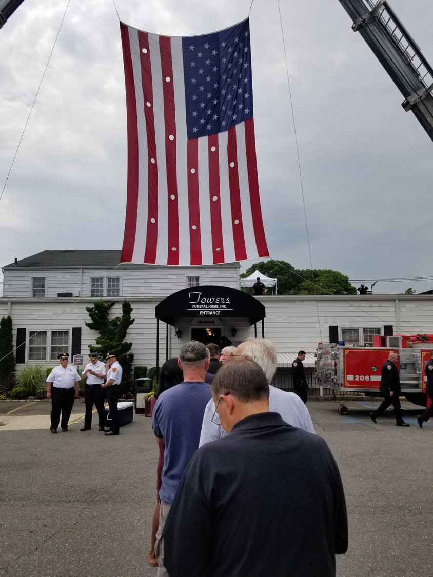 An American flag was displayed between two fire truck ladders outside of Towers Funeral Home in Oceanside during Alvarez's wake on Tuesday.