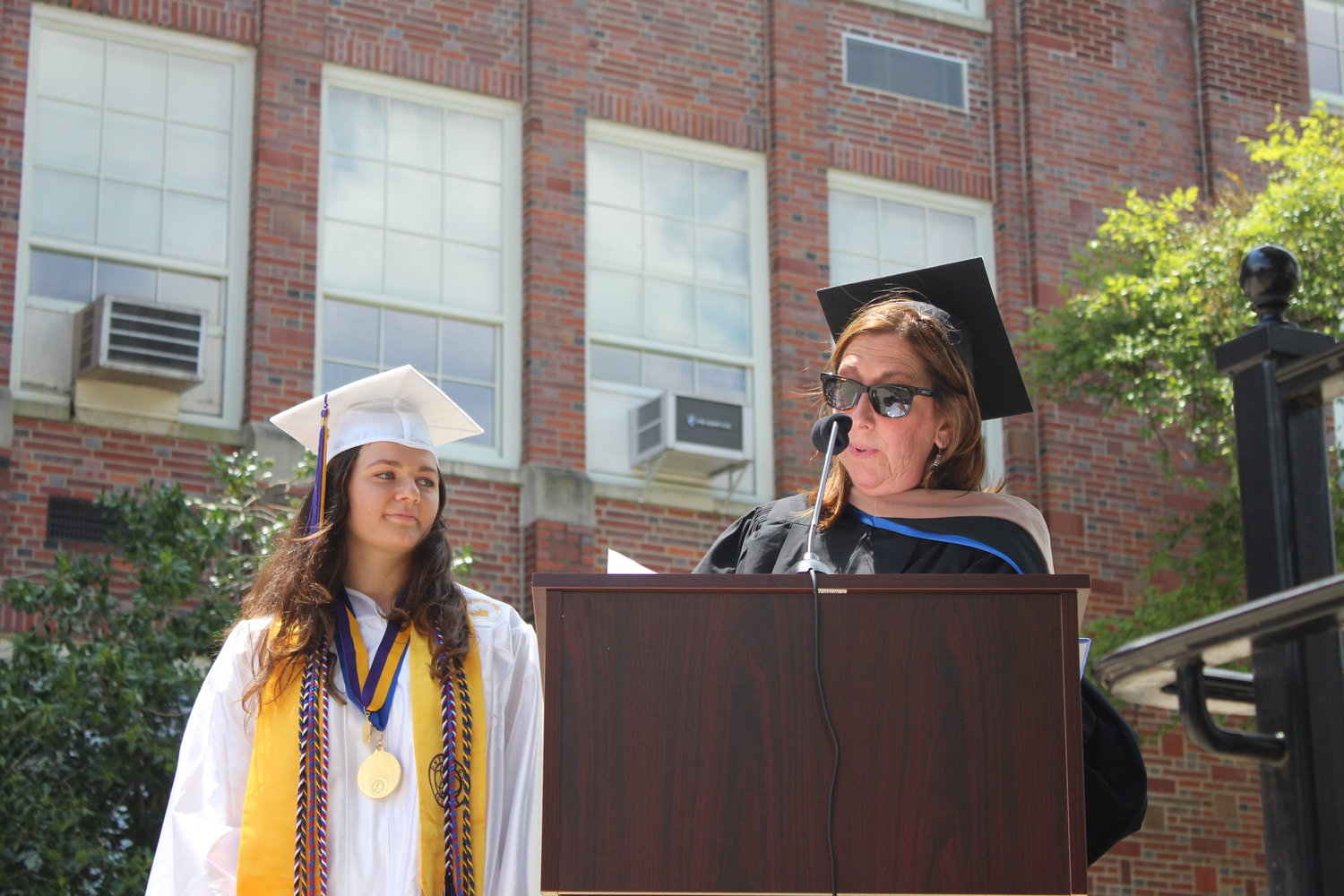 Oyster Bay High School Principal Ms. Sharon Lasher presents the Beekman Medal, the highest honor bestowed upon a graduating senior, to Maggie Ford.