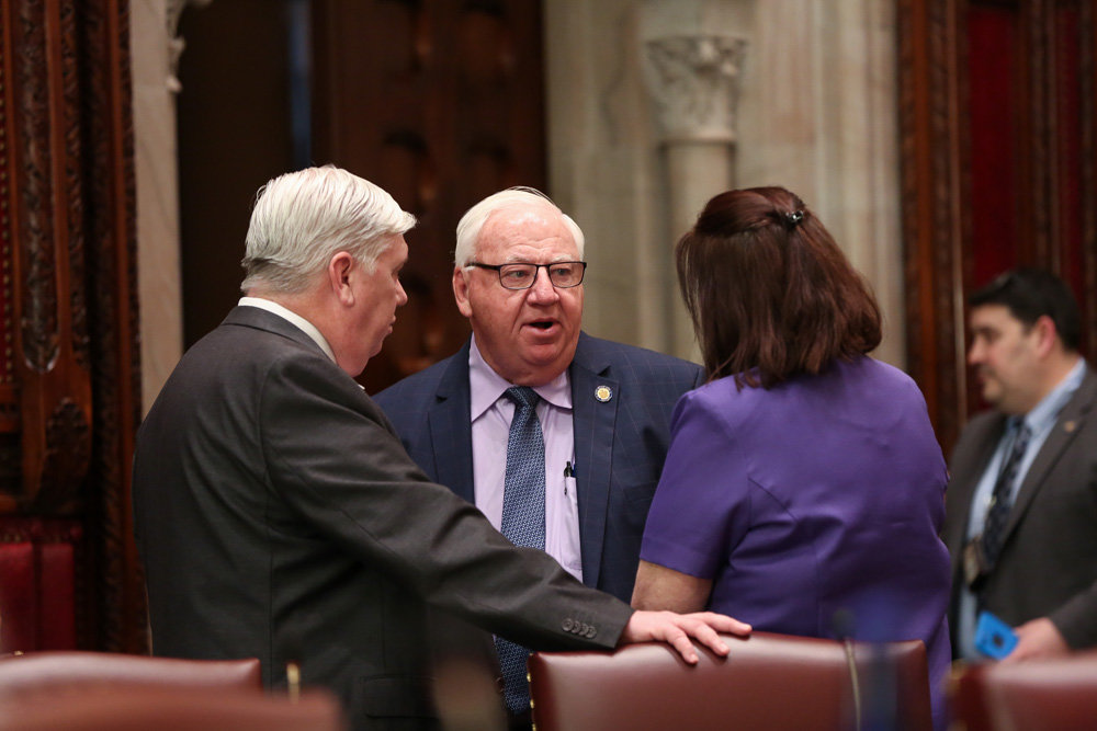 State Sen. John Brooks chatted with his staff on the Senate floor before the passage of Bill S.1687.