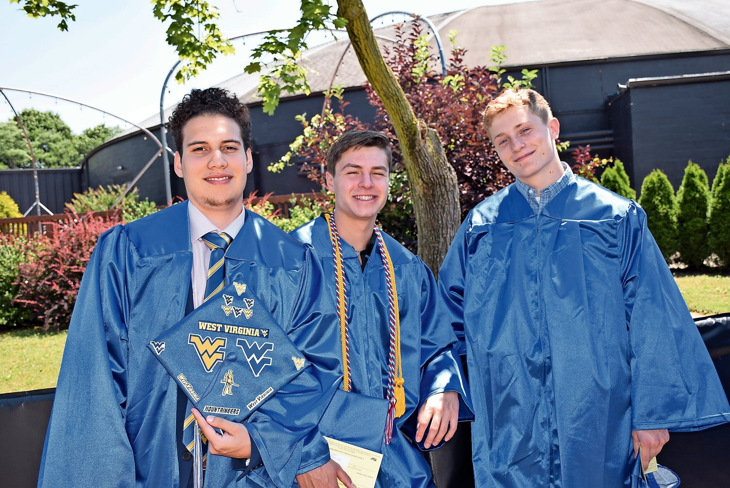 Harrison Valdes, left, proudly displayed his future university with peers Nicholas Turrini and James Thomann.