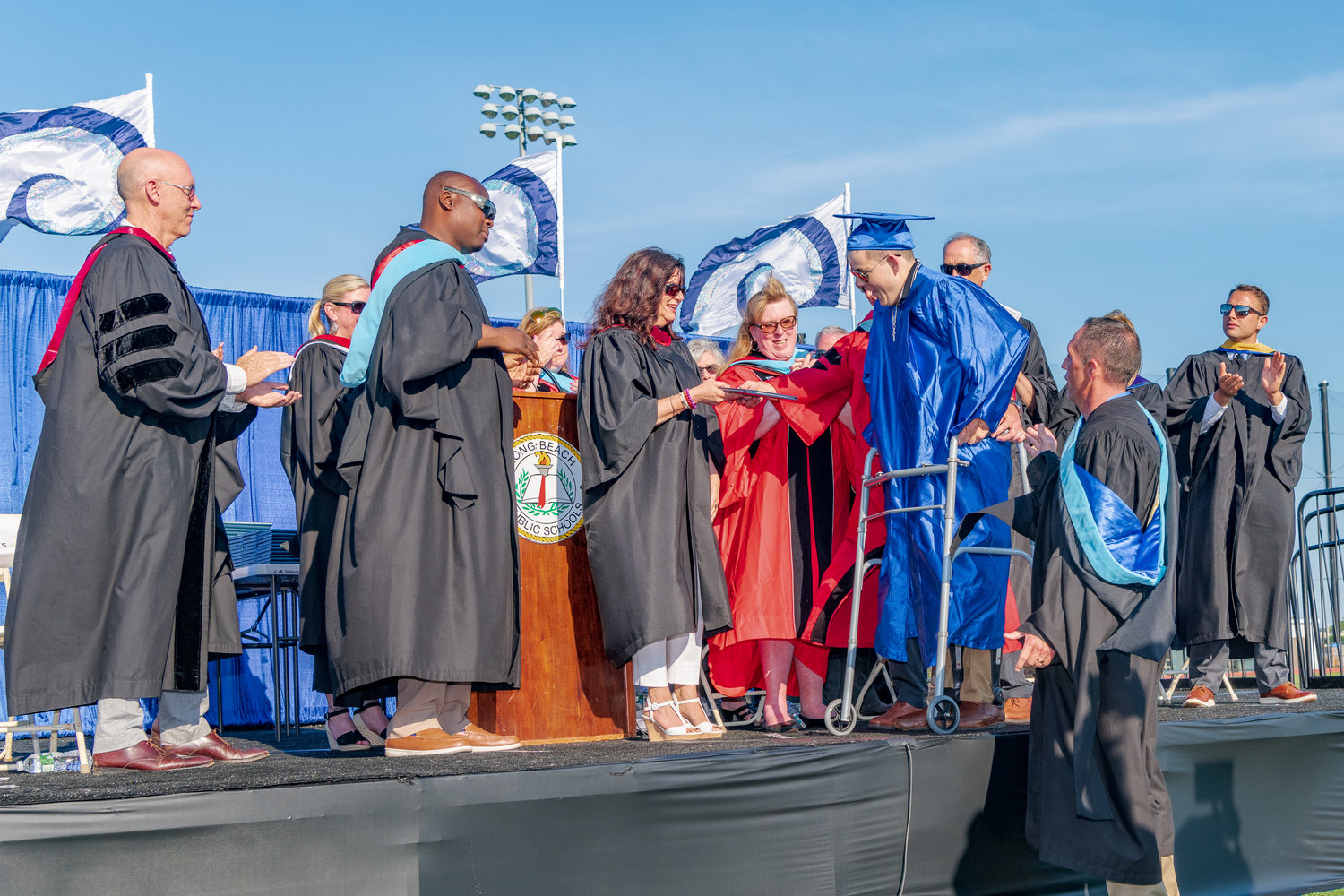 Long Beach High School Robert Browne, 18, who was paralyzed in a surfing accident in 2014, received a standing ovation on June 26 when he left his wheelchair to walk across the stage and received his diploma.