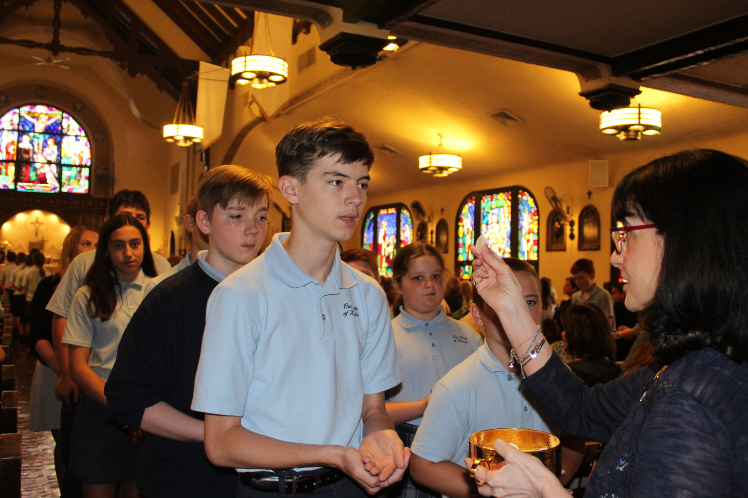 Murphy, who is also a Eucharistic minister, gave communion to Jake Osborne during her final First Friday Devotion last month.