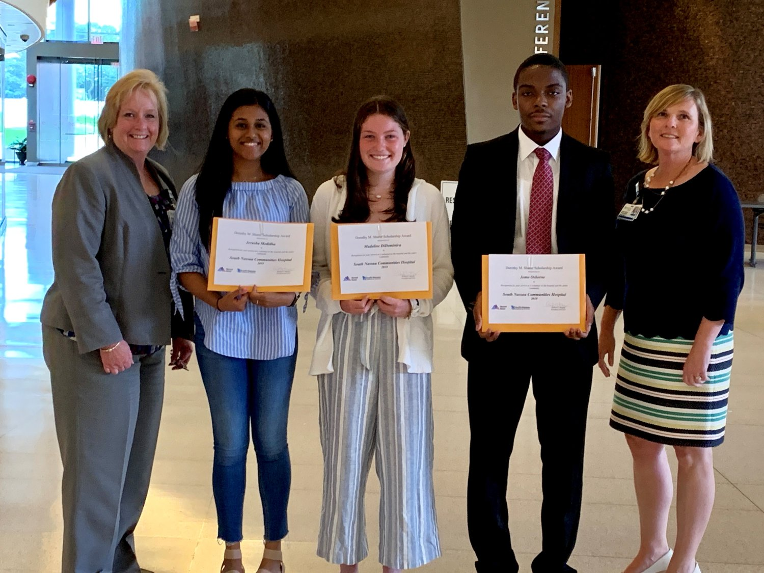 Mary Golden, assistant vice president of human resources, far left, and Anne Marie Fernandez, director of volunteers, far right, presented South Nassau's Dorothy M. Sharer Scholarship to Jerusha Medidha, of Rockville Centre, left, Madeline DiDominica, of Oceanside, and Jomo Osborne, of Baldwin.