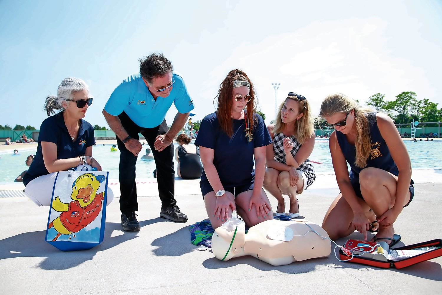 Kim, Stew and Gillen, in back, get low for a closer look at a defibrillator demonstration by Lifeguard Captain Erin McCarthy and Lifeguard Supervisor Ann Marie Hawkins.