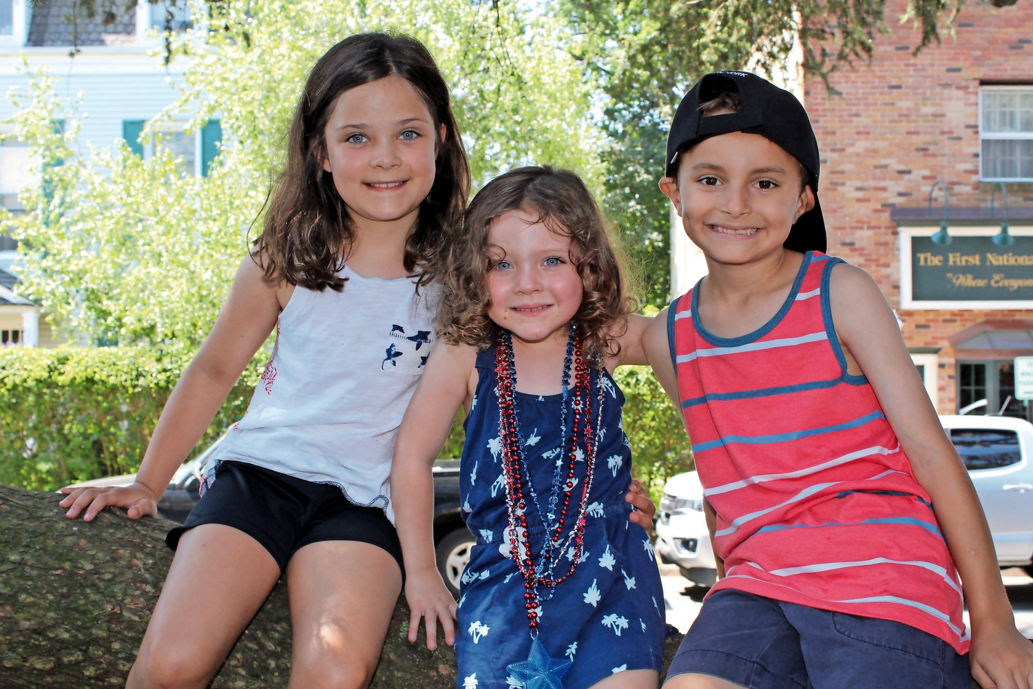 Addie, left, and Lily Sanak sat in the shade on the village green to beat the heat with their friend Lucas D'Altorio.