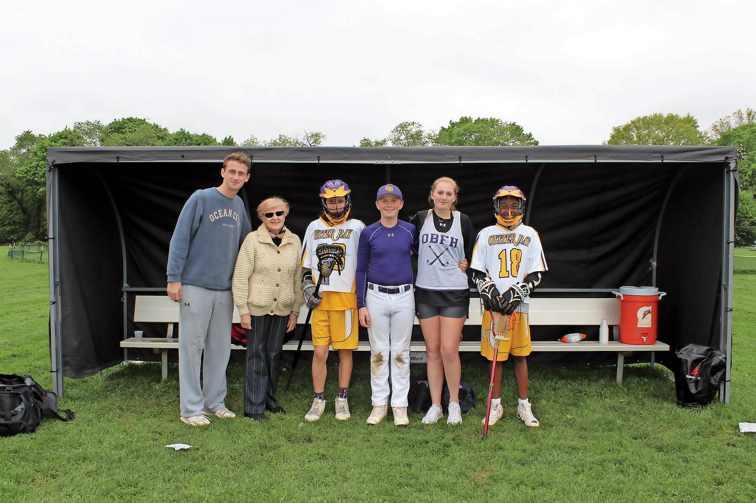 Sean O'Toole, Colette Coyne Melanoma Awareness Campaign founder Colette Coyne, Caleigh, and Colin O'Toole and a few lacrosse players who will benefit from the new sun shields.