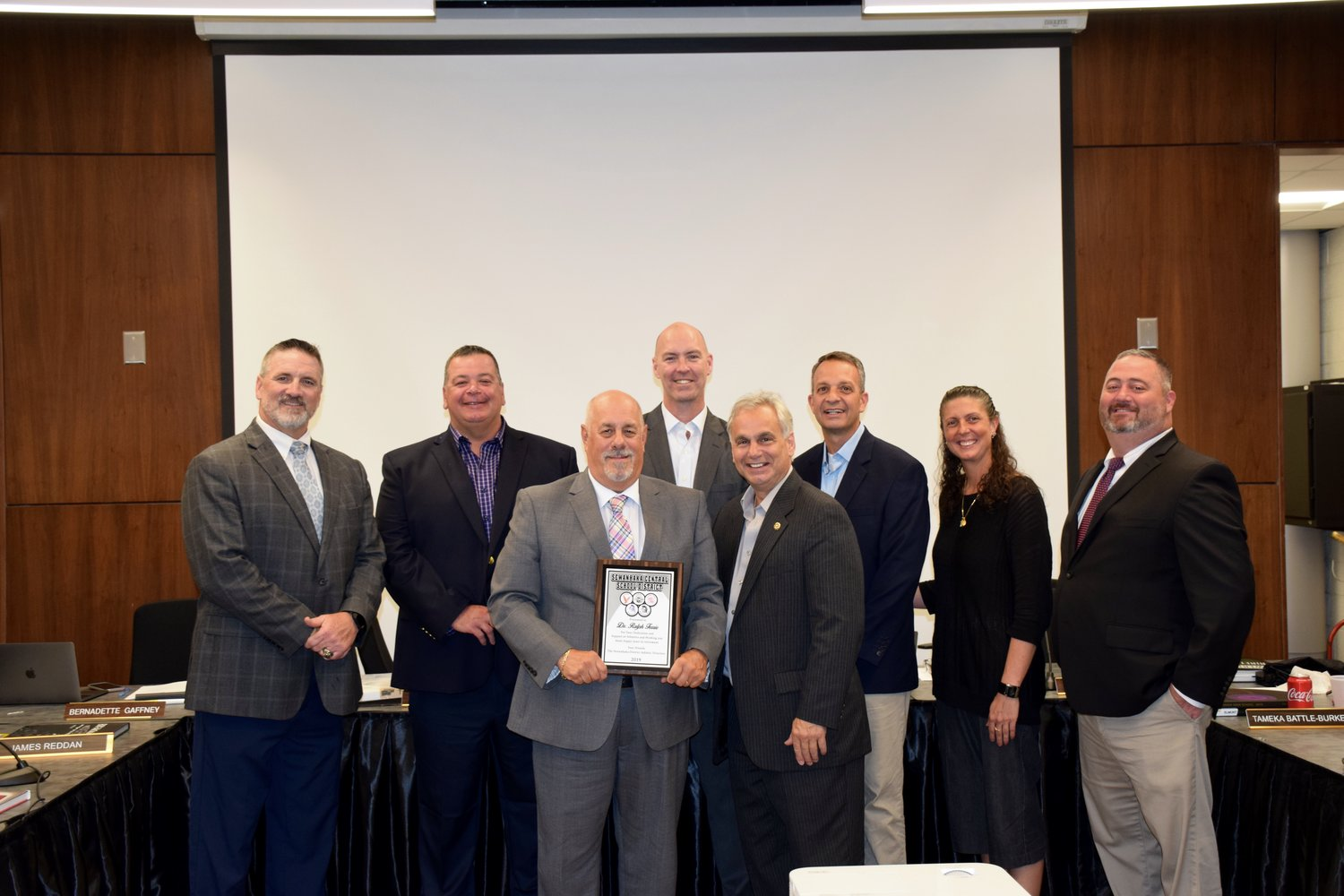 Sewanhaka Central High School District officials and athletic directors bid farewell to retiring Superintendent Ralph Ferrie, holding the plague, on June 18.