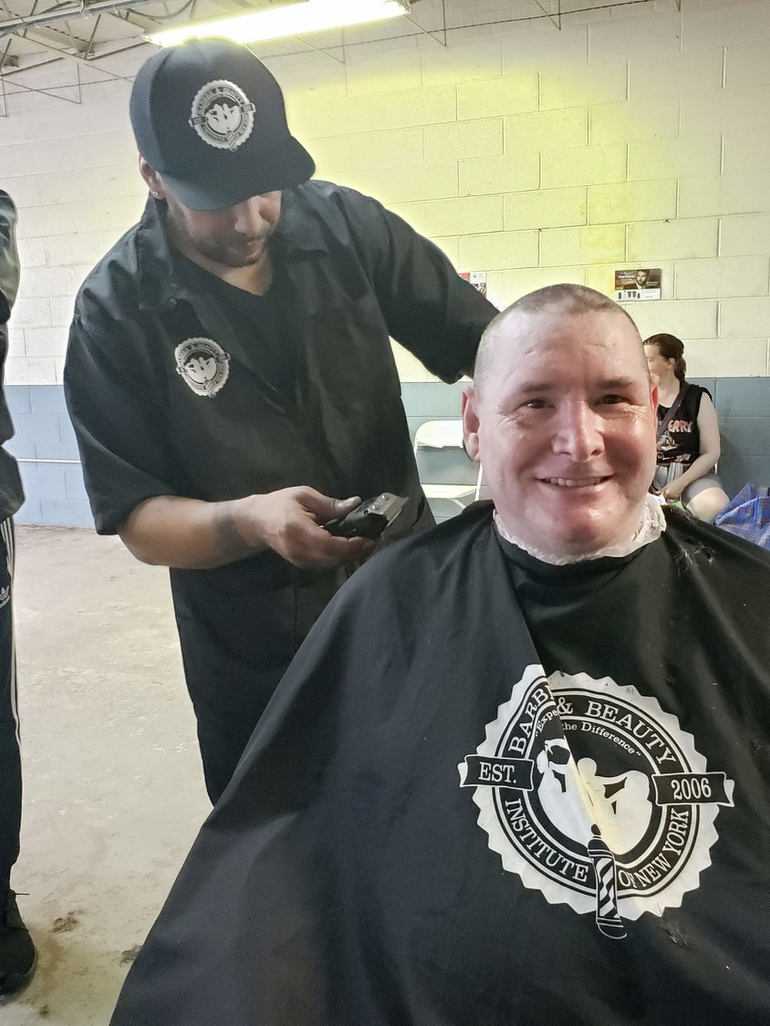 David Cornell, from Lynbrook, a Marine Corps veteran who fought in Operation Desert Storm in Kuwait, had his hair cut by Will Torres, of Queens Village, a student at the Barber and Beauty Institute of New York.