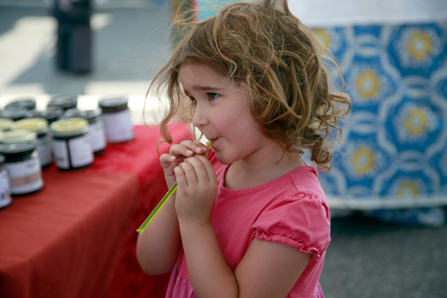 Linden Shamey, 3, sipped a honey stick at the Valley Stream Farmers Market — the village's first — on July 11.