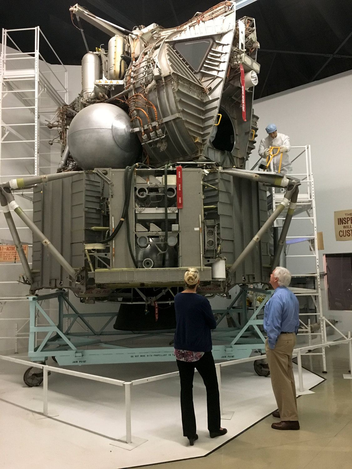 Jennifer Baxmeyer, executive director of the Cradle of Aviation Museum, center, and museum President Andrew Parton with the test lunar module on display.