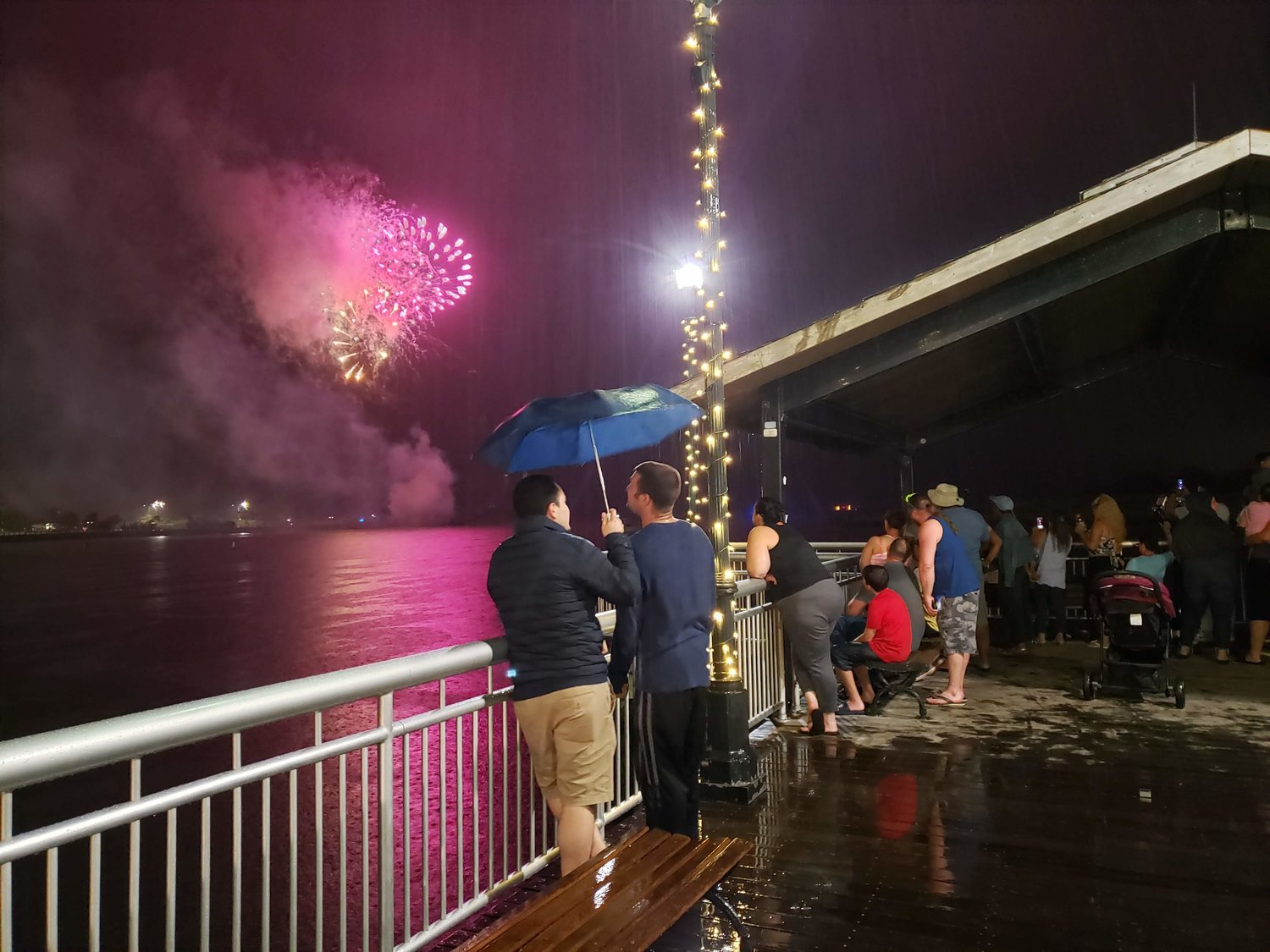 Spectators stood under the Woodcleft Scenic Pier gazebo or shared umbrellas to watch the fireworks in the rain.