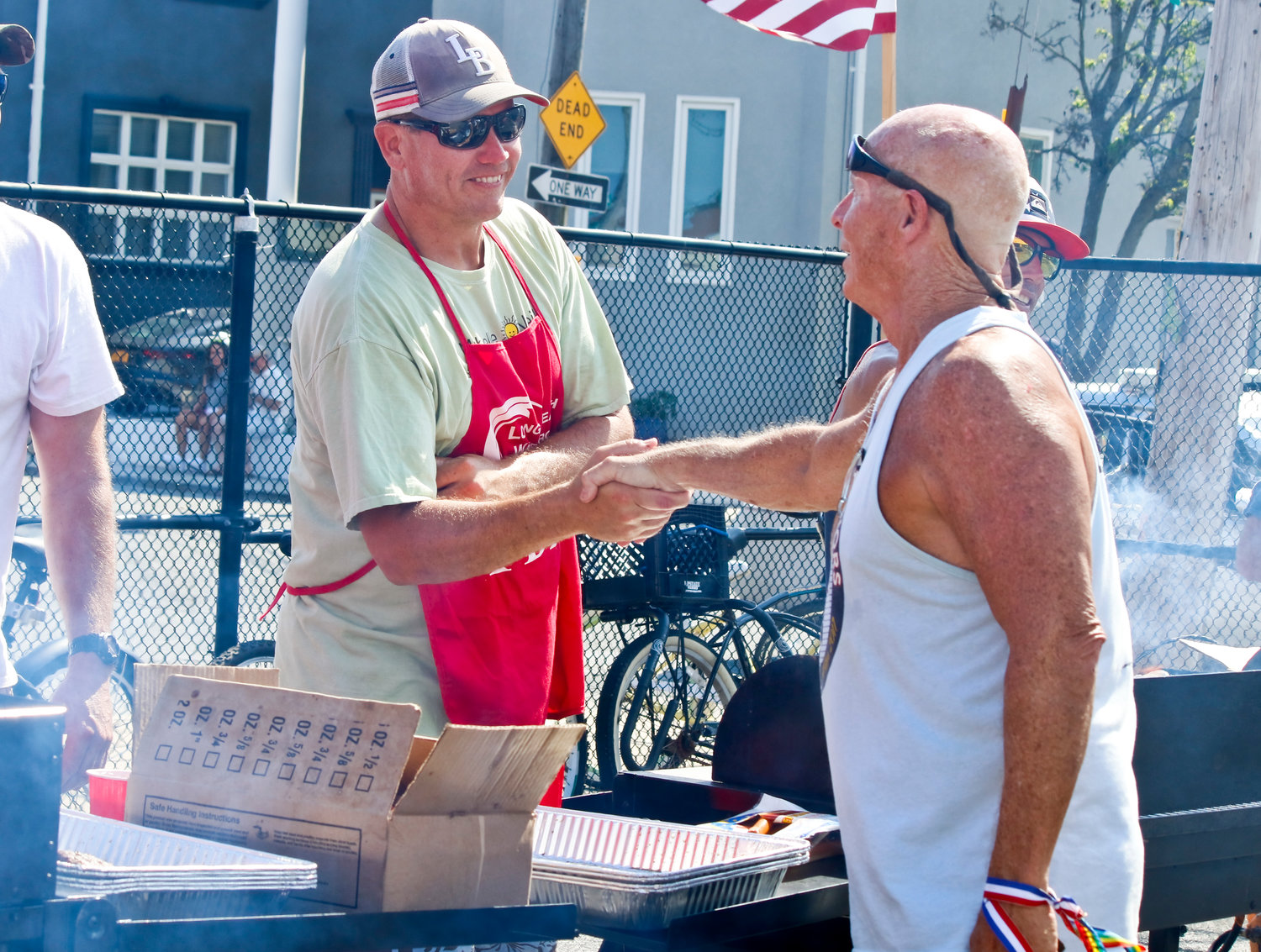 Cook Billy Duffy, left, and other FDNY members prepared barbecue for veterans and their families. Waterfront Warriors co-founder Jerry Snell thanked them for their services.