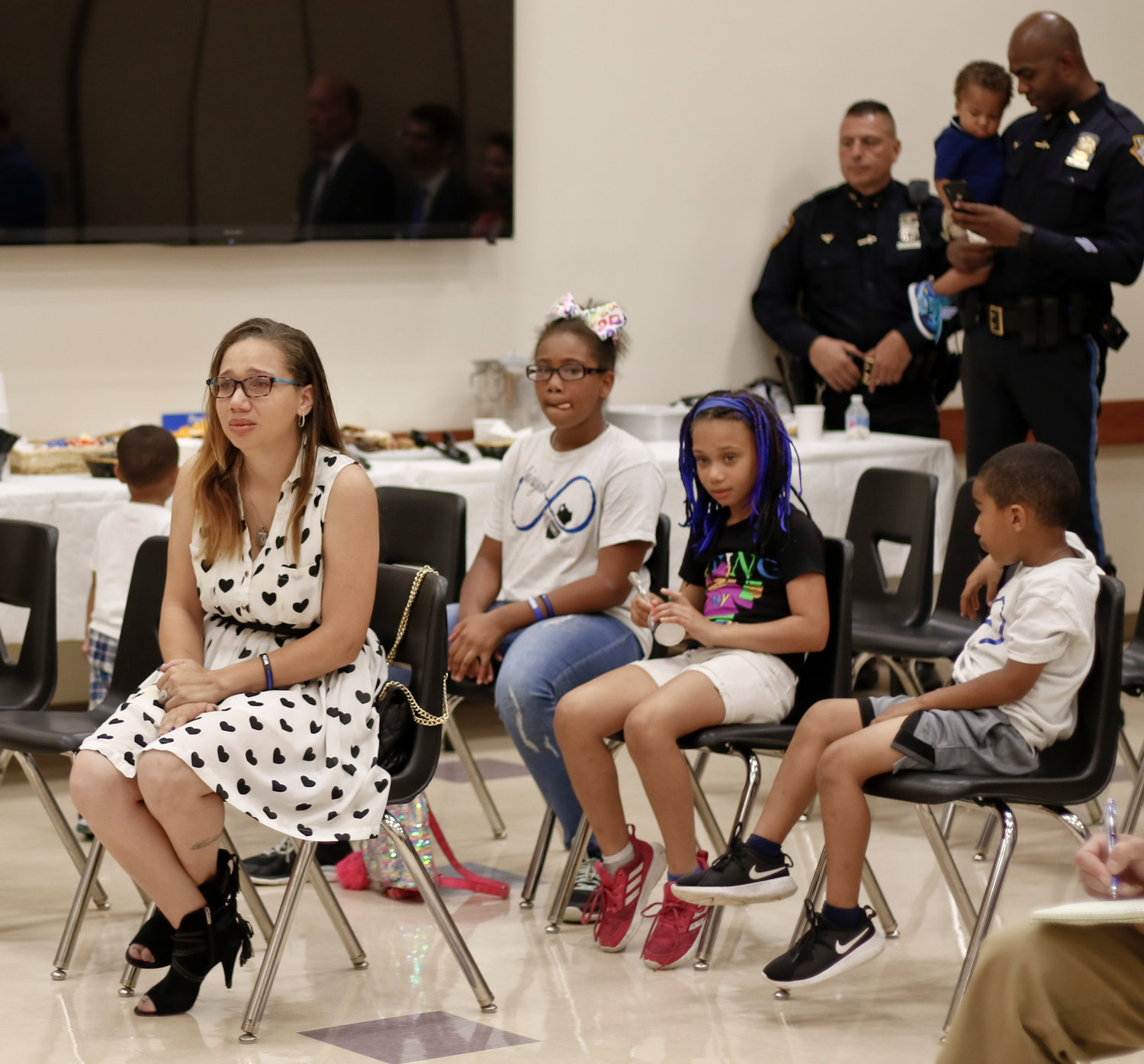 Cecilia Jackson St. Arromand, widow of Elmont NYPD Officer Marc St. Arromand, tearfully listened to remarks from officers of her husband's highway patrol unit as well as Long Island Jewish Valley Stream hospital administrators, with her children Sa'niyah, Calya and Michael.