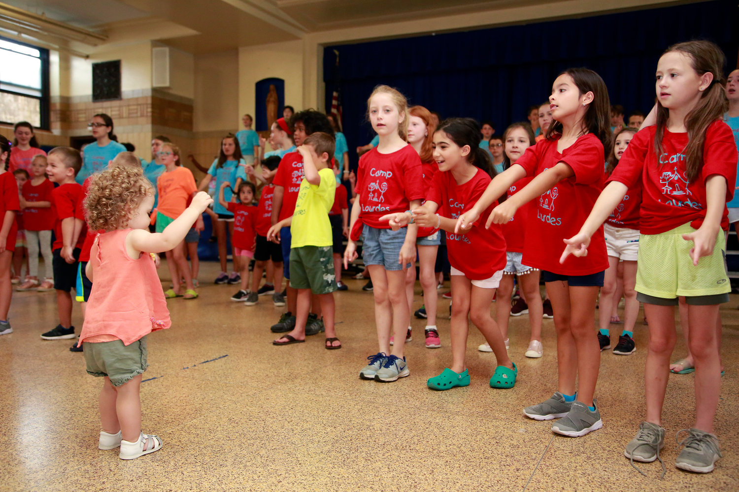 Two-year-old Ella Kardon, left, took part in a musical rehearsal at Camp Lourdes' annual celebration at Our Lady of Lourdes parish on July 10.