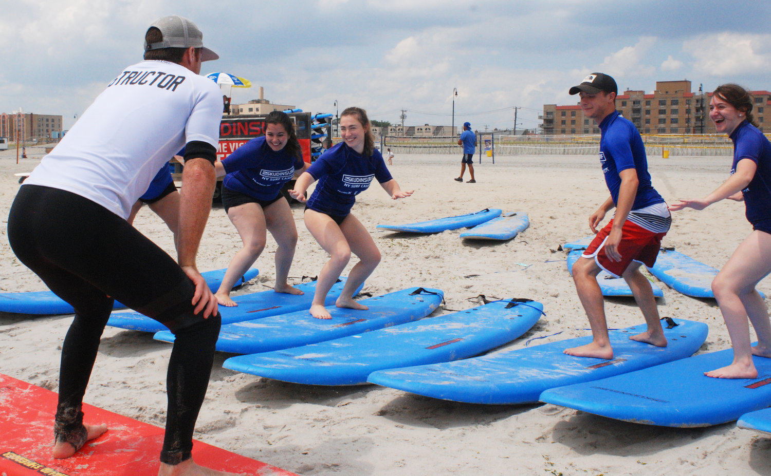 The Herald crew began their surfing lesson by learning how to steady themselves on their boards. At left were, at front, instructor Ian Skudin, and from left, Herald staffers Alyssa Seidman and Bridget Downes, intern Frank Gargano, and staffer Melissa Koenig.