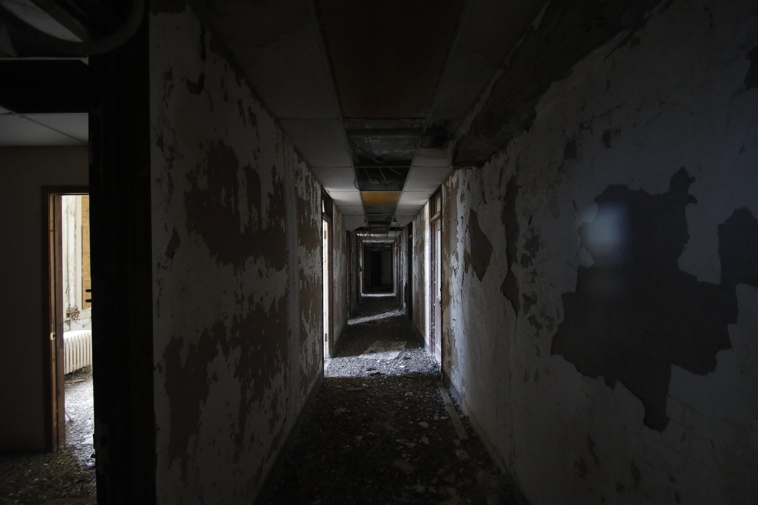 The hallways of each floor were covered in chipped paint, fallen ceiling ties, splintered wires and filth.