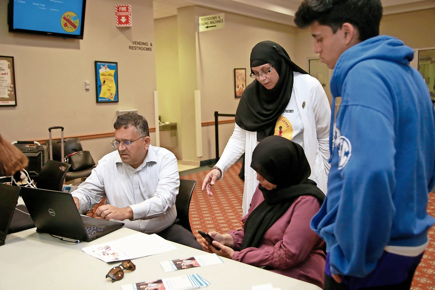 Chaplain Jamillah Mozawalla, right, helped Murtaza and Rumayla Bhalloo fill out their application.