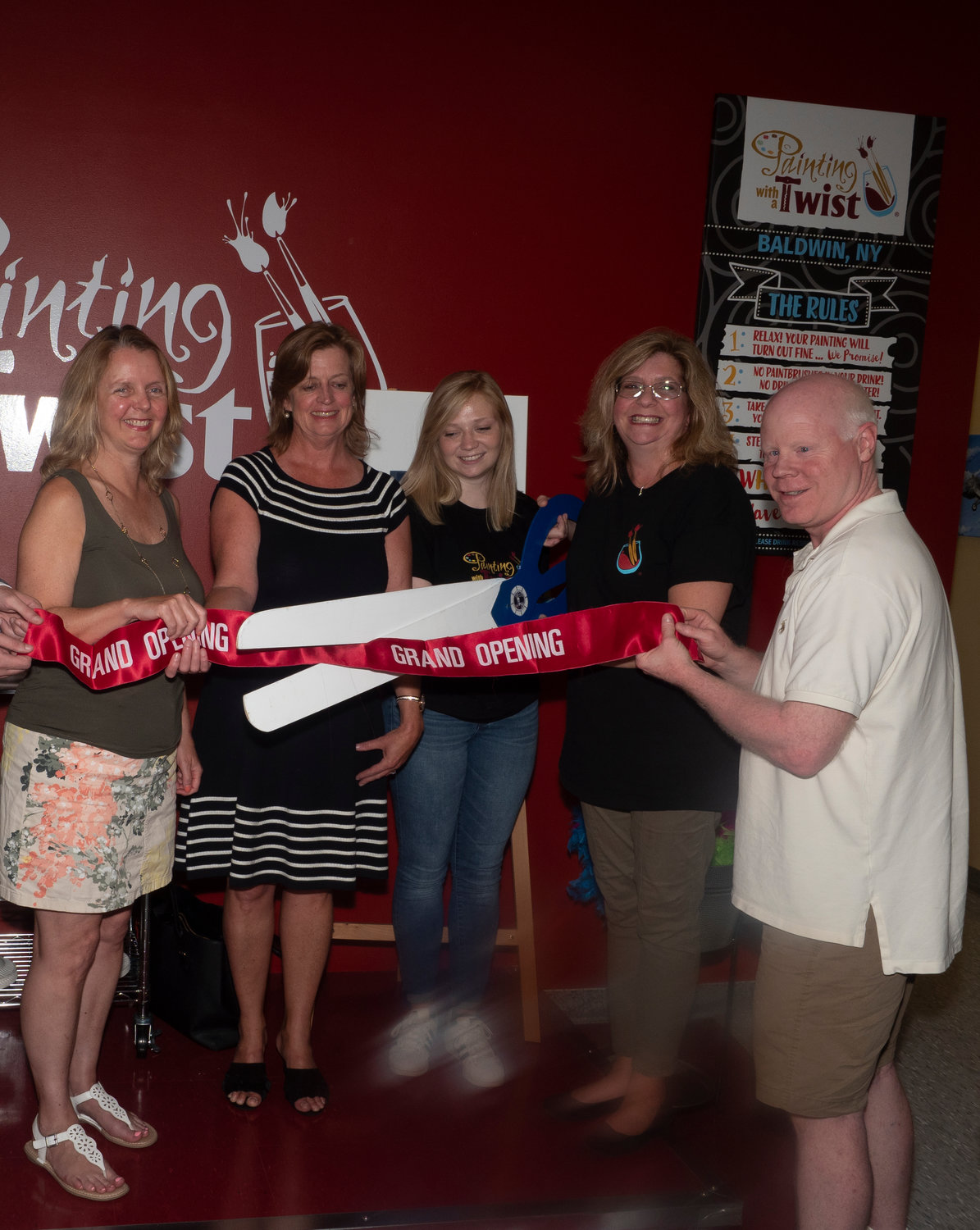 Nassau County Legislator Debra Mule, left, State Assemblywoman Judy Griffin, Katherine Bove, store manager, Joanne Bove, store owner, and Michael Leake, Baldwin Chamber of Commerce board member, cut the ribbon to mark the opening of Painting with a Twist on July 17.